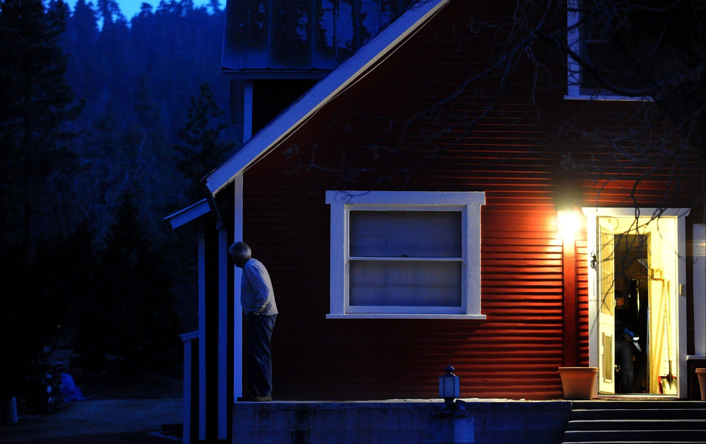 Resident John Laszloffy glances outside his home along Switzerland Avenue as officers look for murder suspect, former Los Angeles Police Department Officer Christopher Dorner, Thursday, Feb. 7, 2013, in Big Bear Lake, Calif.