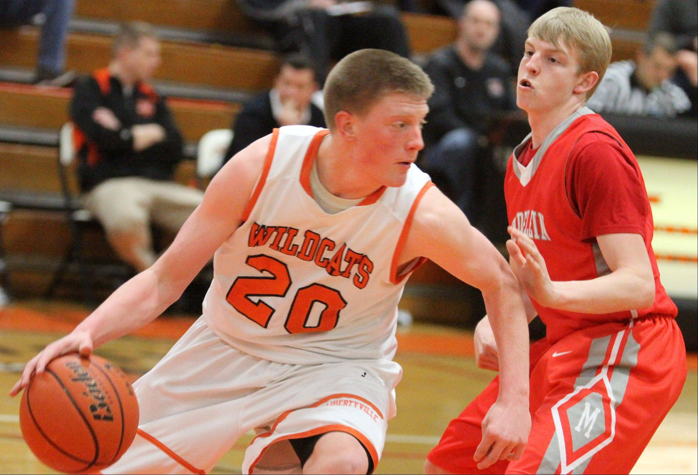 Libertyville guard Jack Lipp looks for running room after grabbing a defensive rebound against Mundelein at Libertyville on Friday.