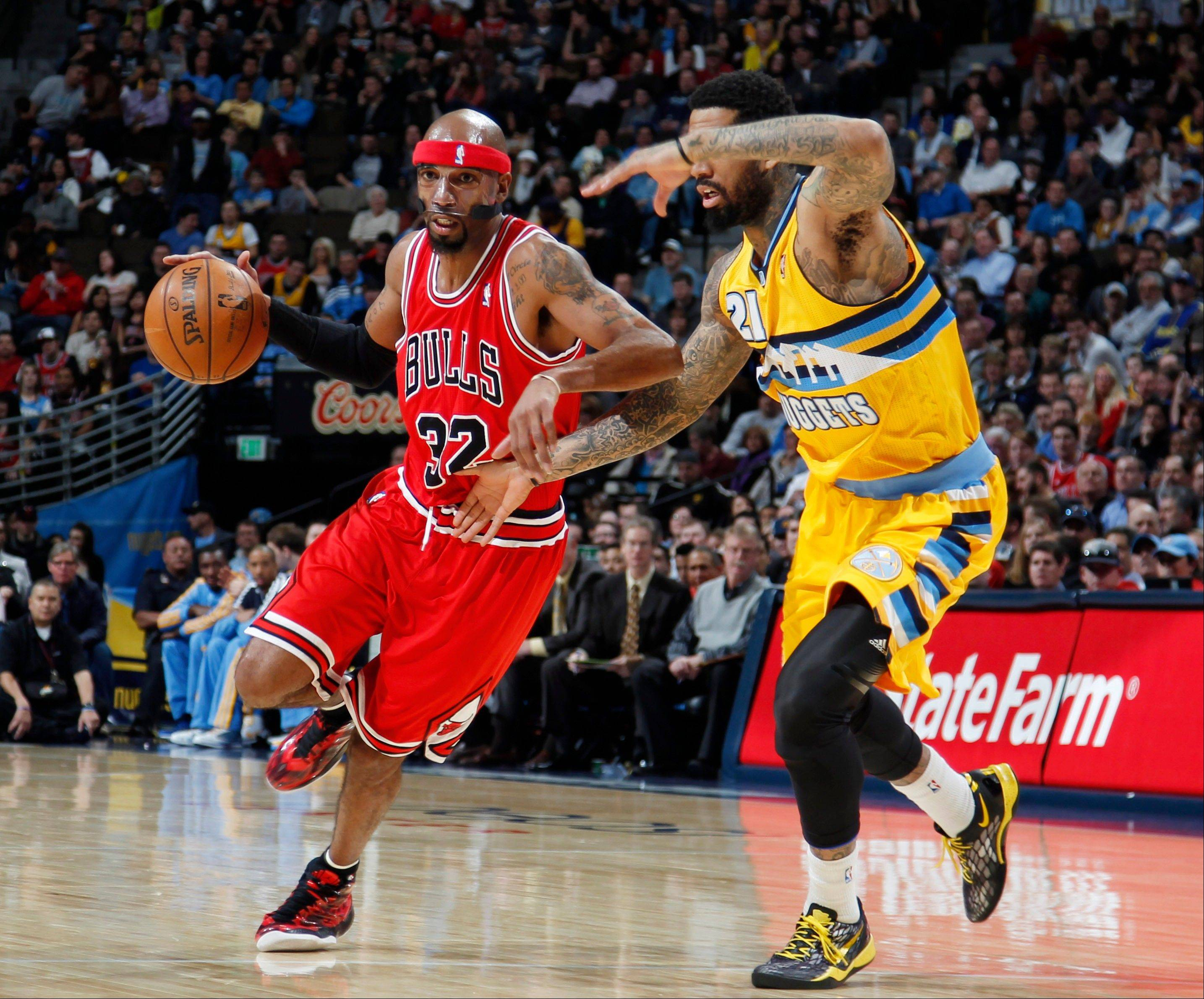 Chicago Bulls guard Richard Hamilton, left, works ball inside past Denver Nuggets forward Wilson Chandler in the first quarter of an NBA basketball game in Denver on Thursday, Feb. 7, 2013. (AP Photo/David Zalubowski)