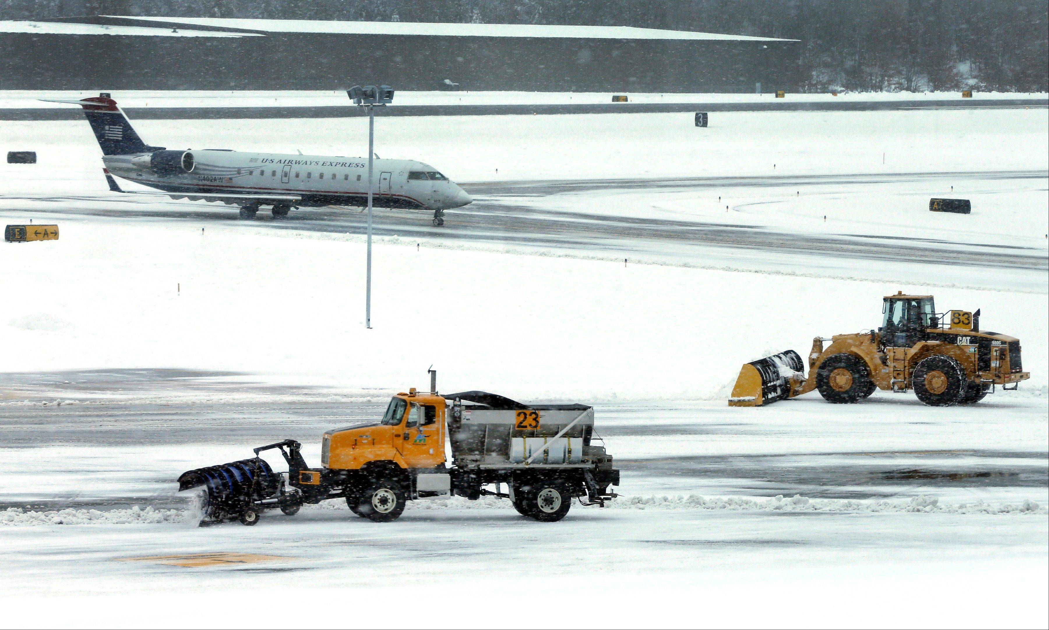 In this Thursday, Dec. 27, 2012 photo, snow is cleared on a runway as a plane taxis into Manchester-Boston Regional Airport in Manchester, N.H. As the Northeast braces for its largest winter storm in more than a year, airlines are already employing a strategy that has served them well in recent years: Cancel flights early and keep planes, crews and passengers away from snowed-in airports.