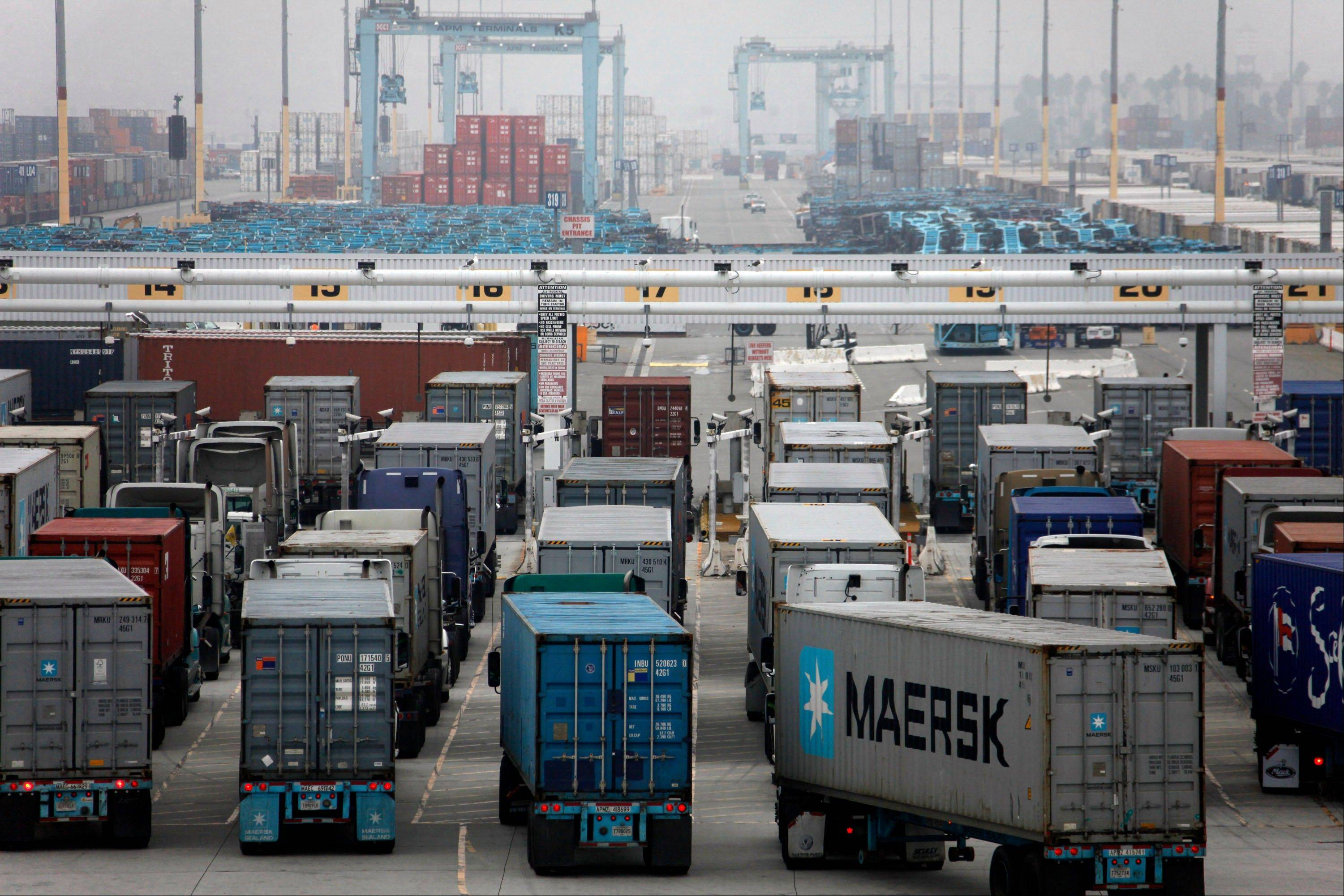 Trucks wait to be loaded at the Port in Los Angeles. U.S. wholesalers cut their stockpiles slightly in December while their sales were unchanged, suggesting businesses were cautious at the end of a weak quarter.