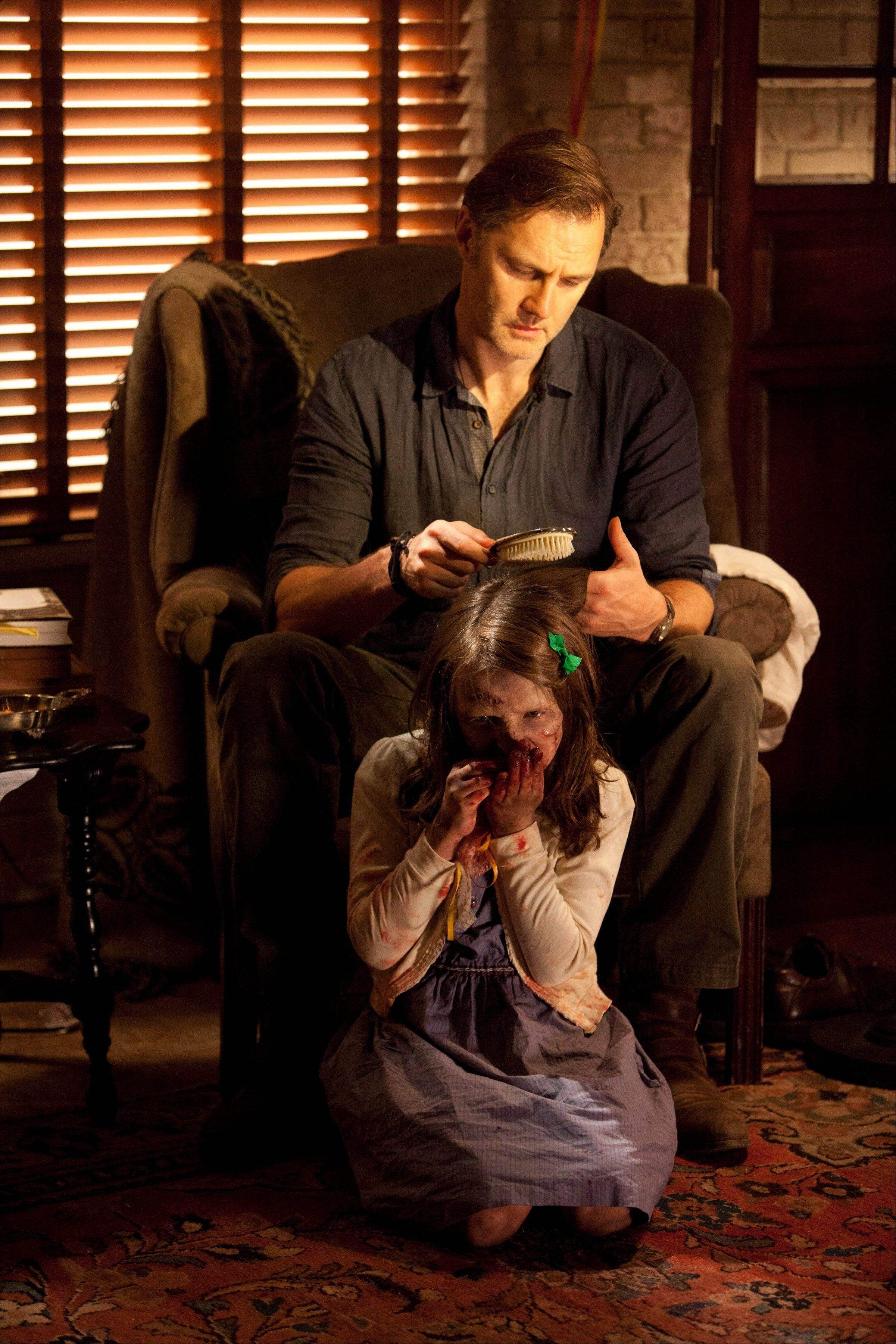 "The Governor (David Morrisey) brushes the hair of his undead daughter Penny (Kylie Szymanski) during the first part of the third season of ""The Walking Dead."" The popular zombie series returns for another eight episodes at 8 p.m. Sunday, Feb. 10."