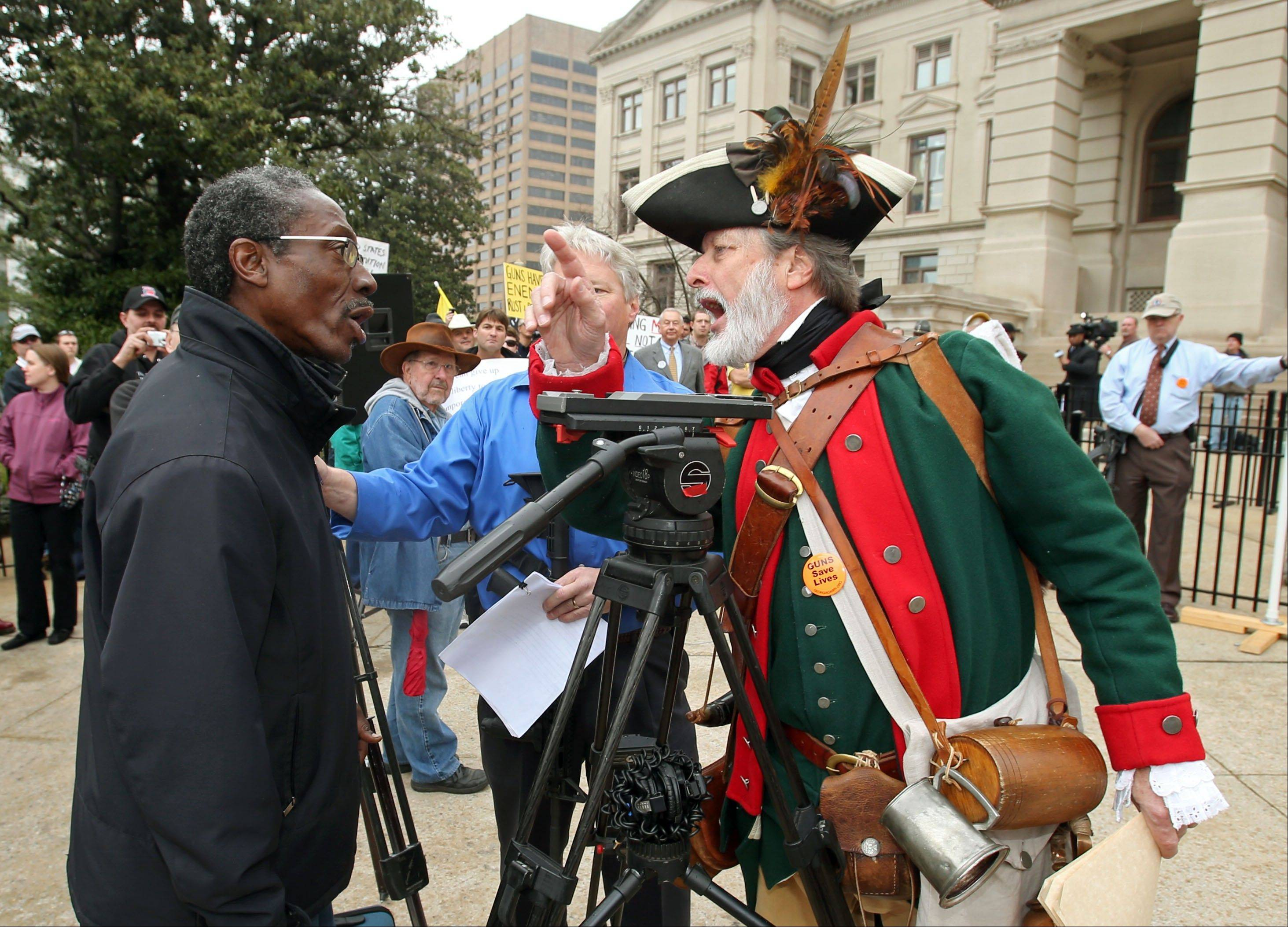 William Temple, of Brunswick, Ga., wearing revolutionary attire, right, argues with a man Friday during the Georgia State Capitol Pro-Gun Rally at the main entrance to the Georgia State Capitol.