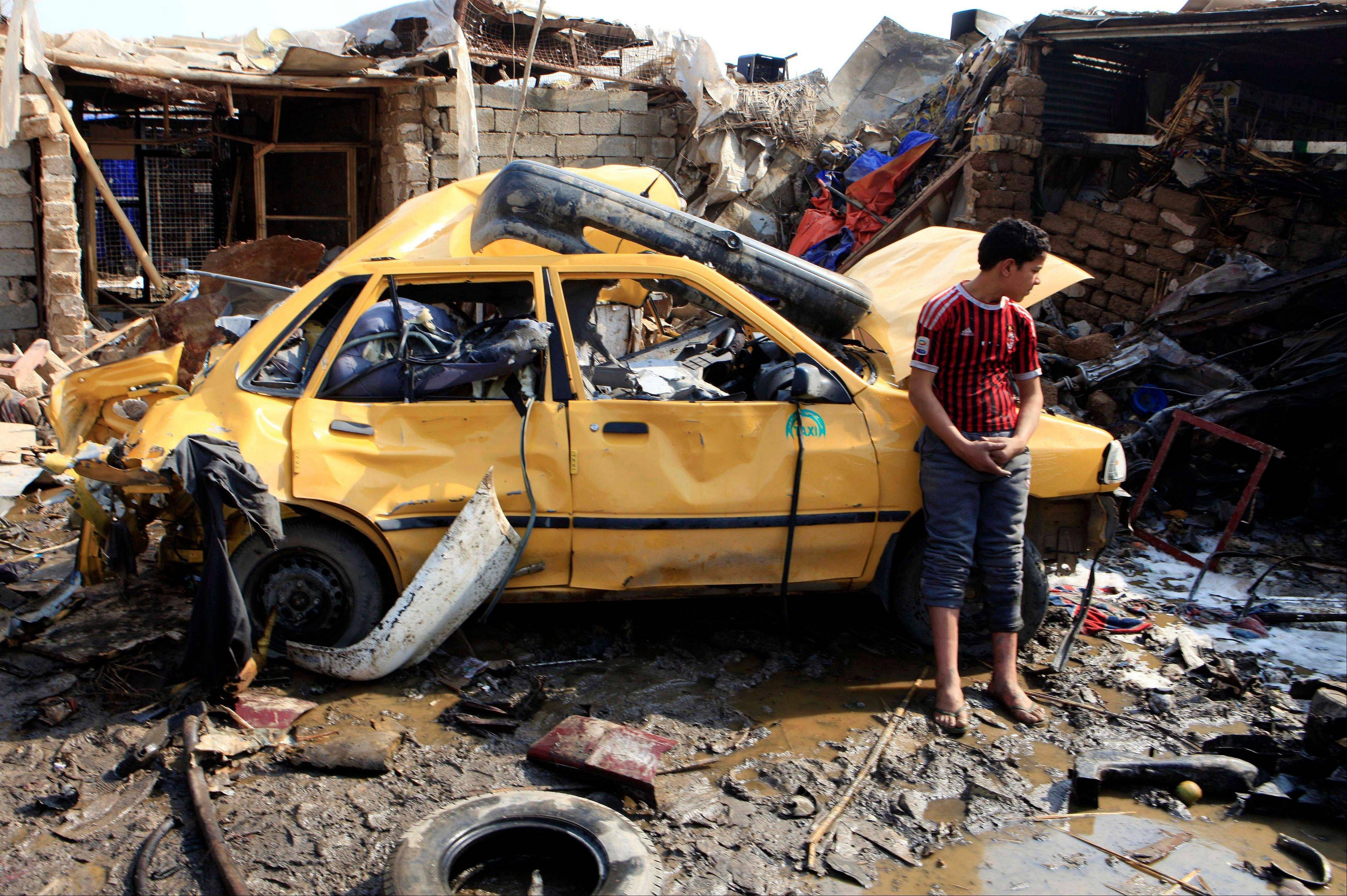 An Iraqi boy stands near a destroyed car at the scene of a car-bomb attack in Baghdad's northern Kazimyah neighborhood, Friday, Feb. 8, 2013. Car bombs struck two outdoor markets in Shiite areas of Iraq on Friday, killing and wounding scores of people, police said.