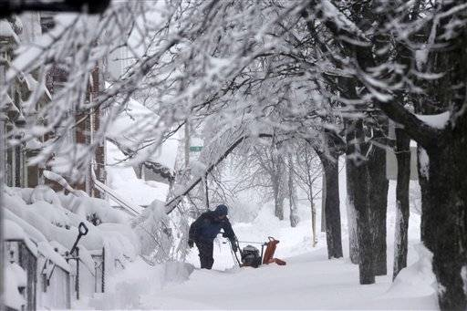 A man clears snow from the front of his home on Third Street in the South Boston neighborhood of Boston on Saturday, Feb. 9, 2013.