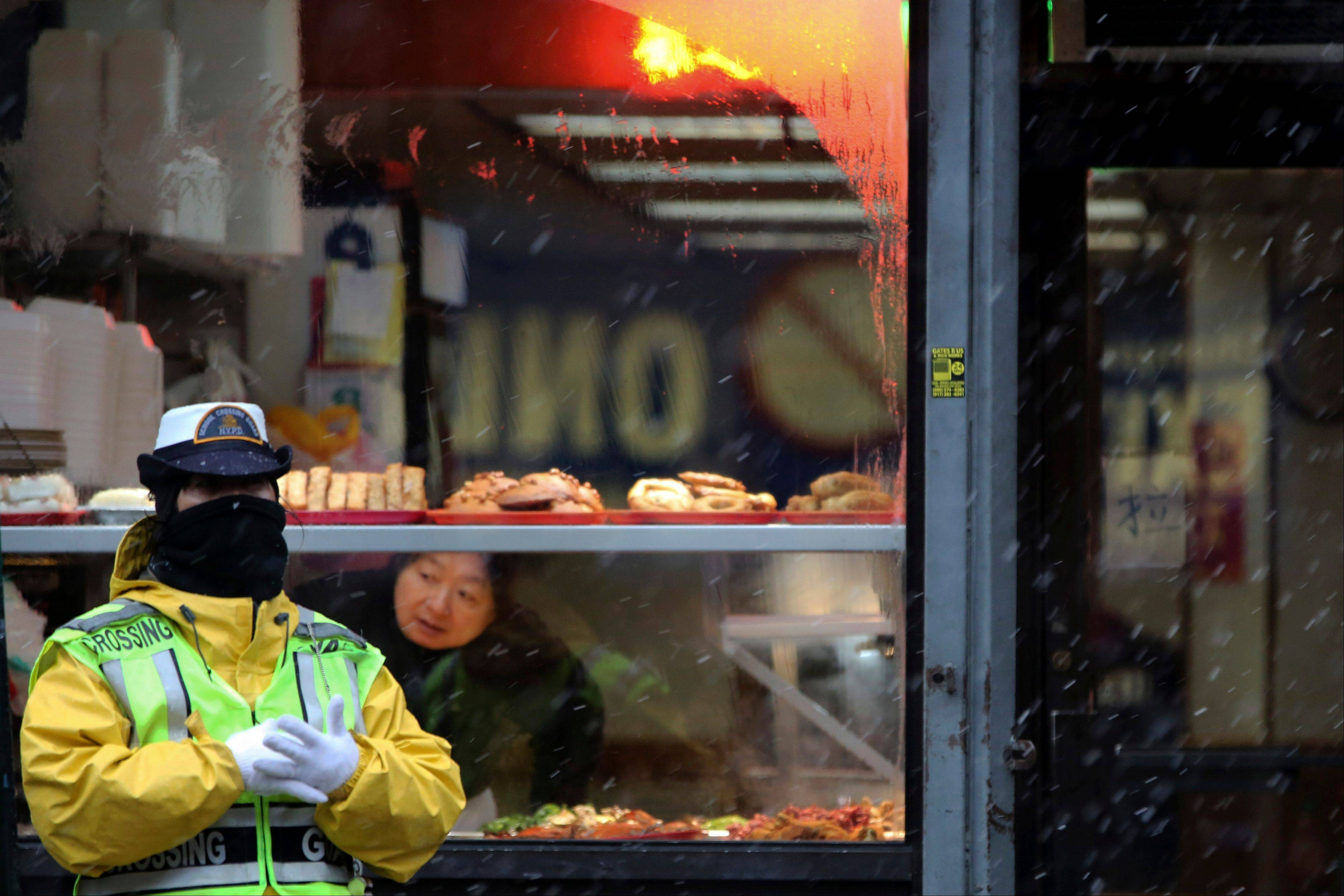 A crossing guard takes cover from the snow under the awning of a restaurant in New York's Chinatown.