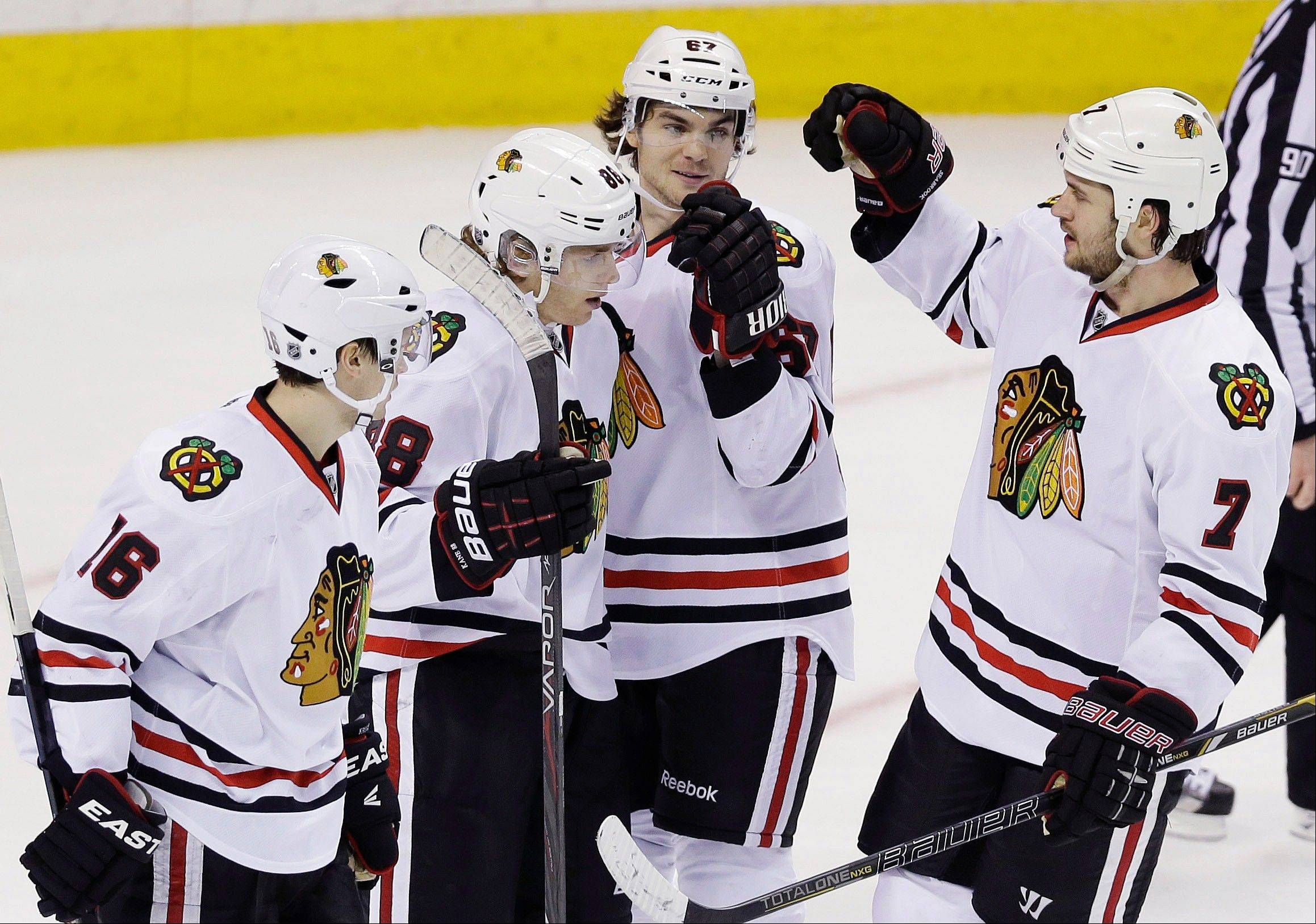 Chicago Blackhawks right wing Patrick Kane, second from left, is congratulated by teammates after scoring against the San Jose Sharks during the third period of an NHL hockey game in San Jose, Calif., Tuesday, Feb. 5, 2013. Chicago won 5-3.