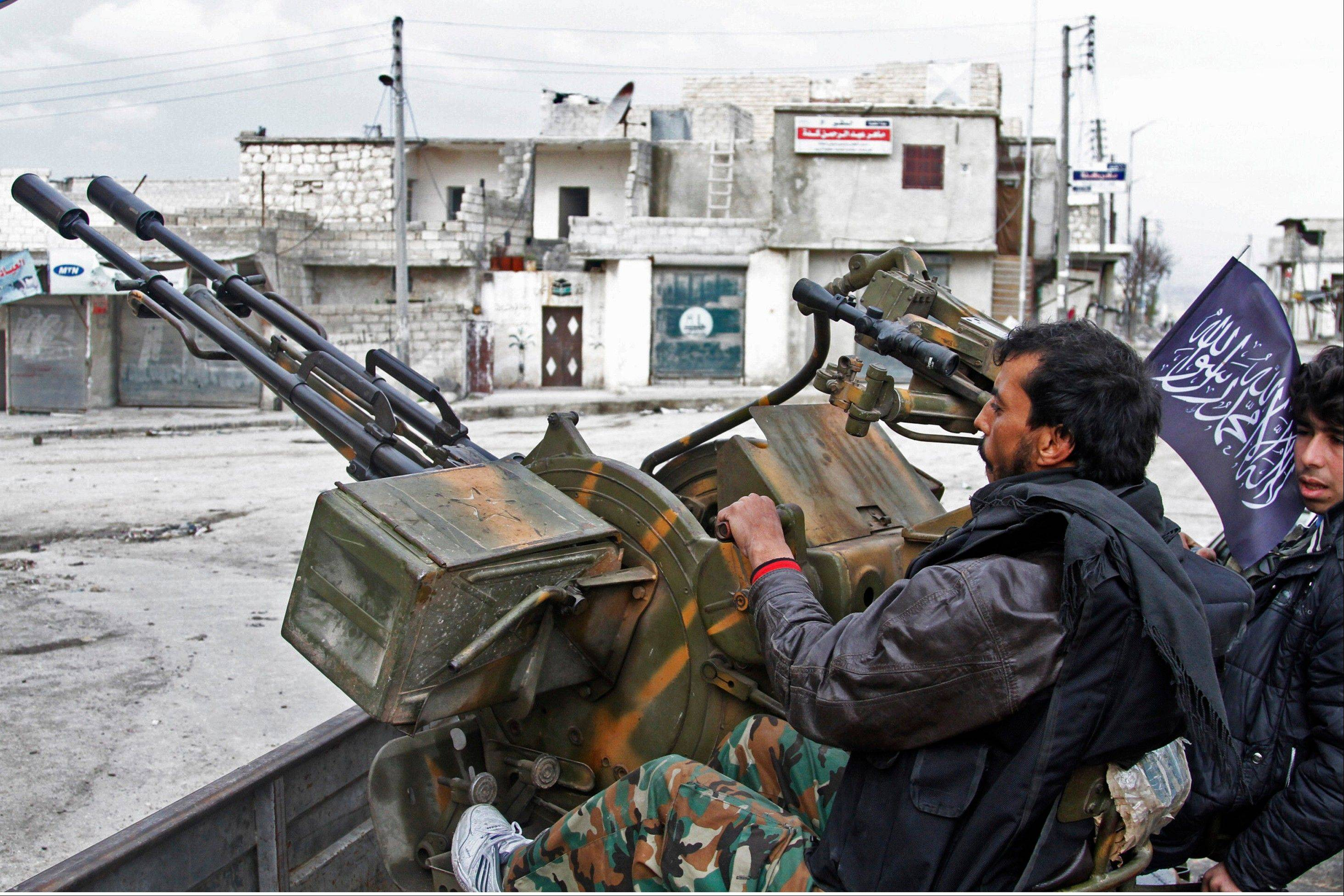 Free Syrian Army fighters sit behind their antiaircraft machine gun in Aleppo, Syria, on Friday. Syrian rebels brought their fight within a mile of the heart of Damascus on Friday, seizing army checkpoints and cutting a key highway with a row of burning tires as they pressed their campaign for the heavily guarded capital, considered the likely endgame in the nearly 2-year-old civil war.