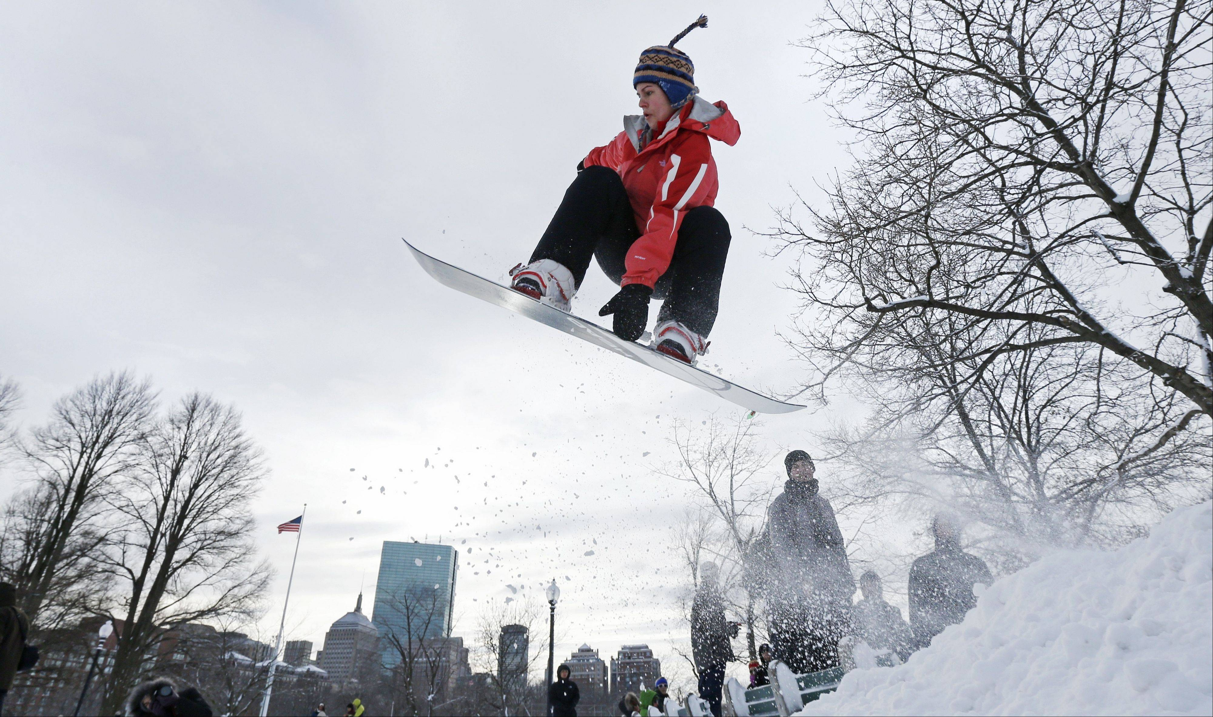 A snowboarder catches some air while taking advantage of a makeshift terrain park on Boston Common in Boston, Saturday. The Boston area received about two feet of snow from a winter storm.