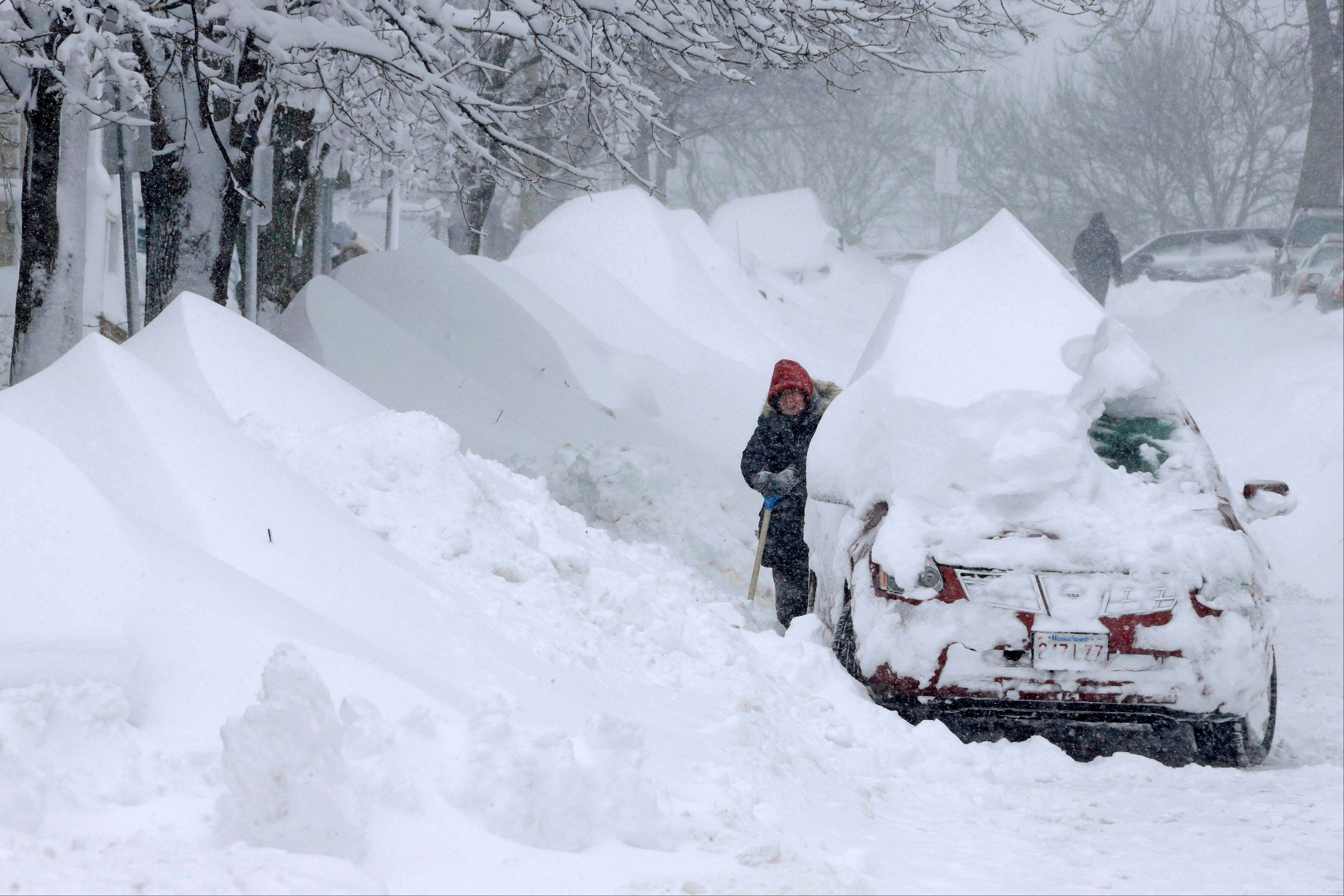 A woman shovels snow to clear out a car on Third Street in the South Boston neighborhood of Boston on Saturday, Feb. 9, 2013. A behemoth storm packing hurricane-force wind gusts and blizzard conditions swept through the Northeast overnight.