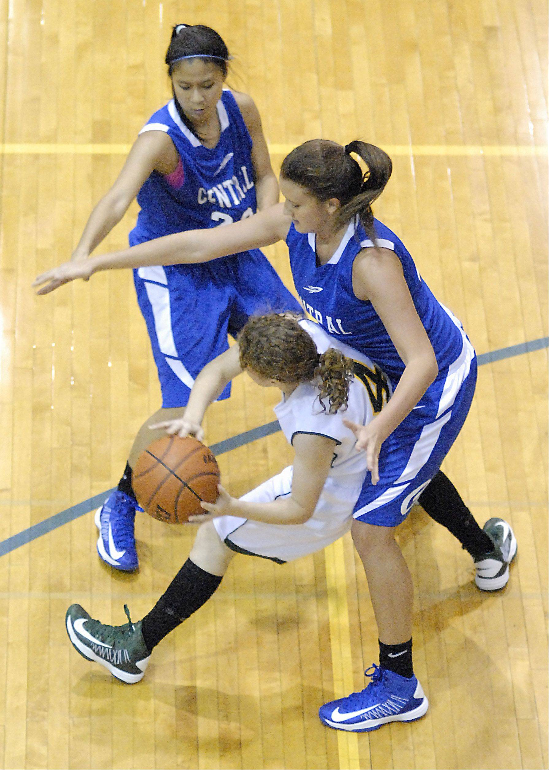 Burlington Central's Camille Delacruz and Alison Colby swarm Crystal Lake South's Carina Madoni during a Christmas tournament game.