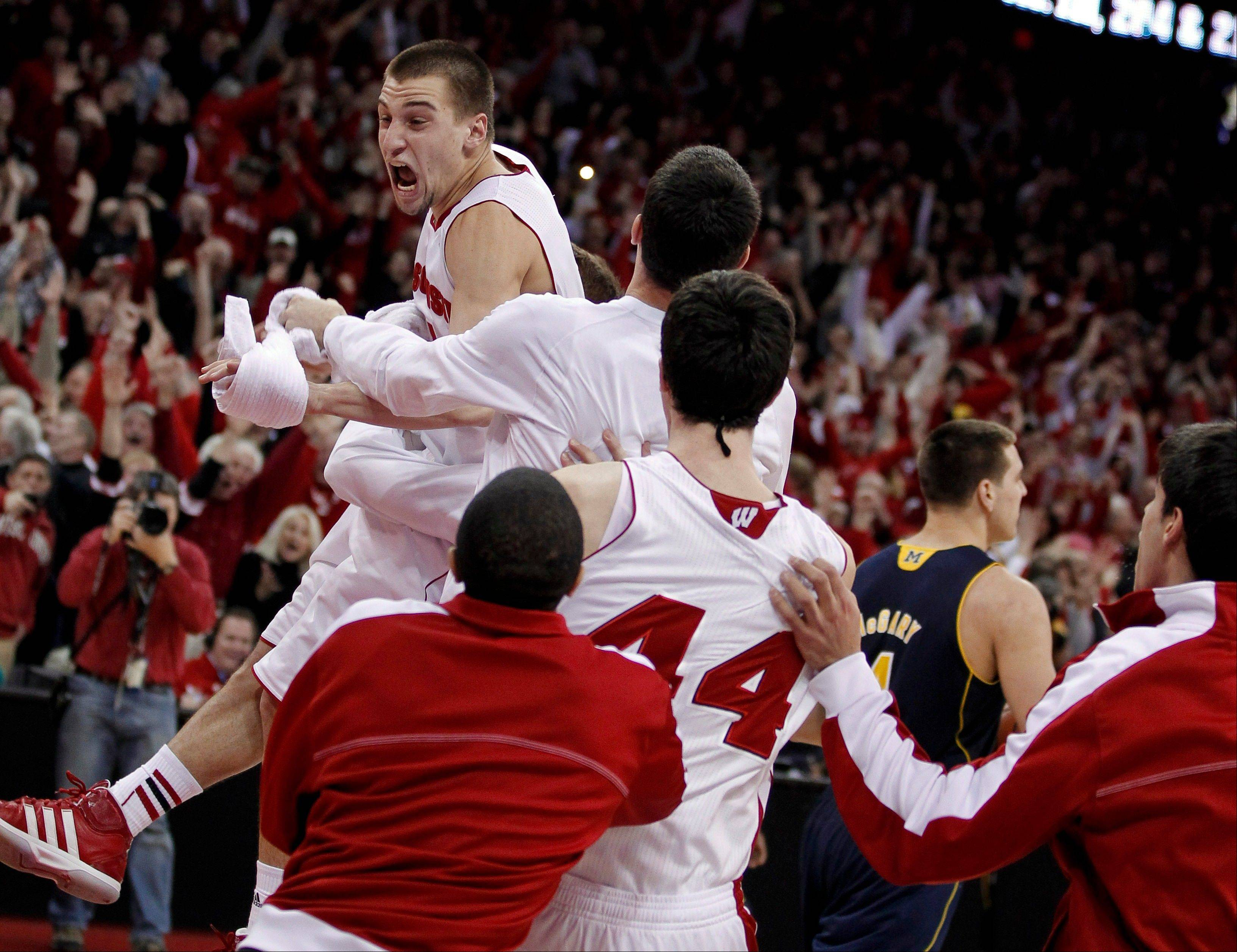 Mundelein native and Wisconsin player Ben Brust, top, celebrates after hitting a 3-point shot in the final second of regulation against Michigan in an NCAA college basketball game Saturday, Feb. 9, 2013, in Madison, Wis. Wisconsin defeated Michigan 65-62 in overtime. (AP Photo/Andy Manis)