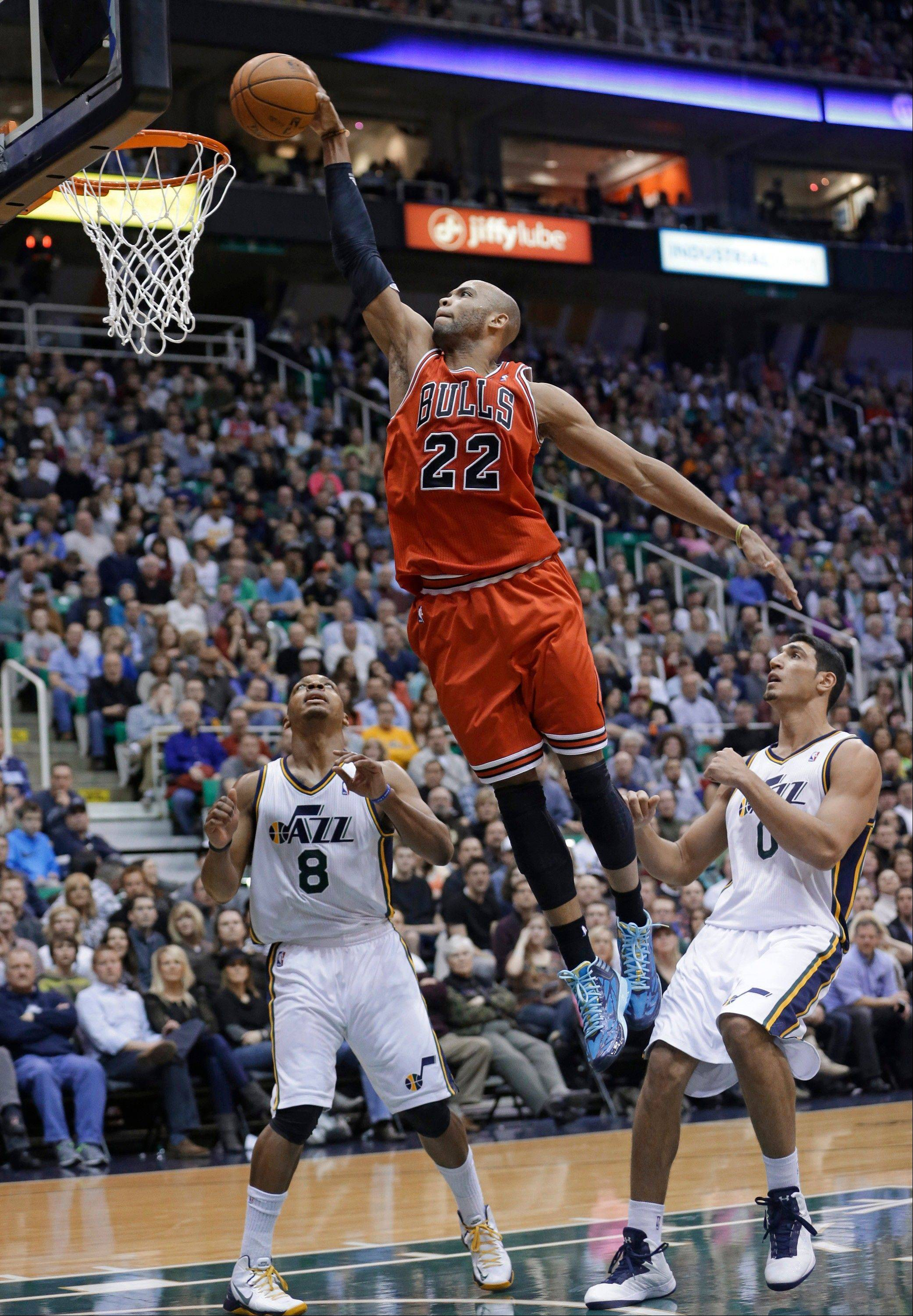 Taj Gibson (22) dunks as Utah's Randy Foye (8) and Enes Kanter (0) watch during the second quarter Friday in Salt Lake City.