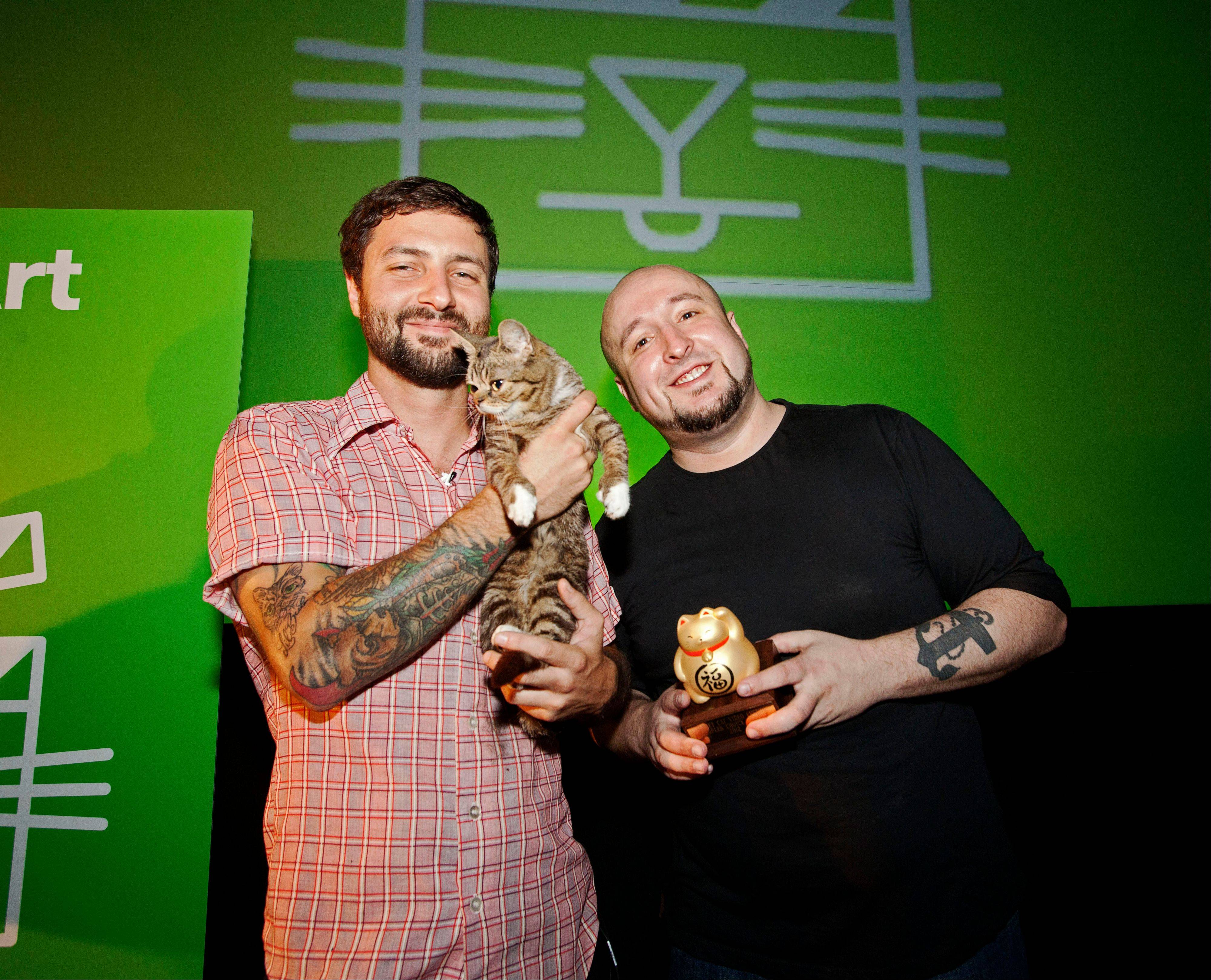 Festival attendee, Mike Bridavsky and his cat, Lil Bub, pose with Golden Kitty Award-winner William Braden at the Walker Art Center Internet Cat Video Festival in Minneapolis.