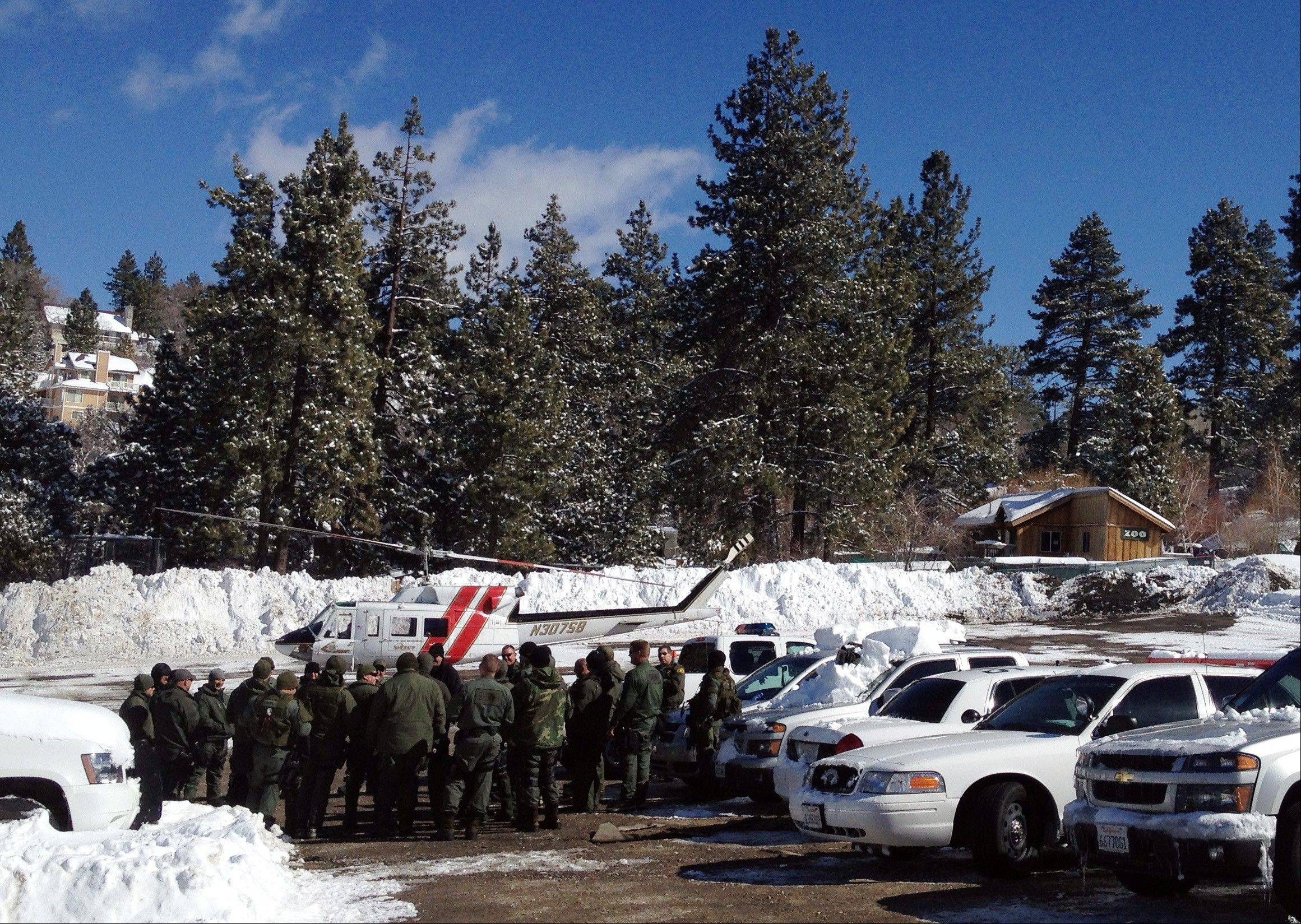 Law enforcement officials gather to discuss plans to resume the search for fugitive Christopher Dorner, Saturday near Big Bear, Calif. More than 100 law enforcement officers, some in armored personnel carriers, hunted Saturday for the former Los Angeles police officer suspected of going on a deadly rampage this week to get back at those he blamed for ending his police career.