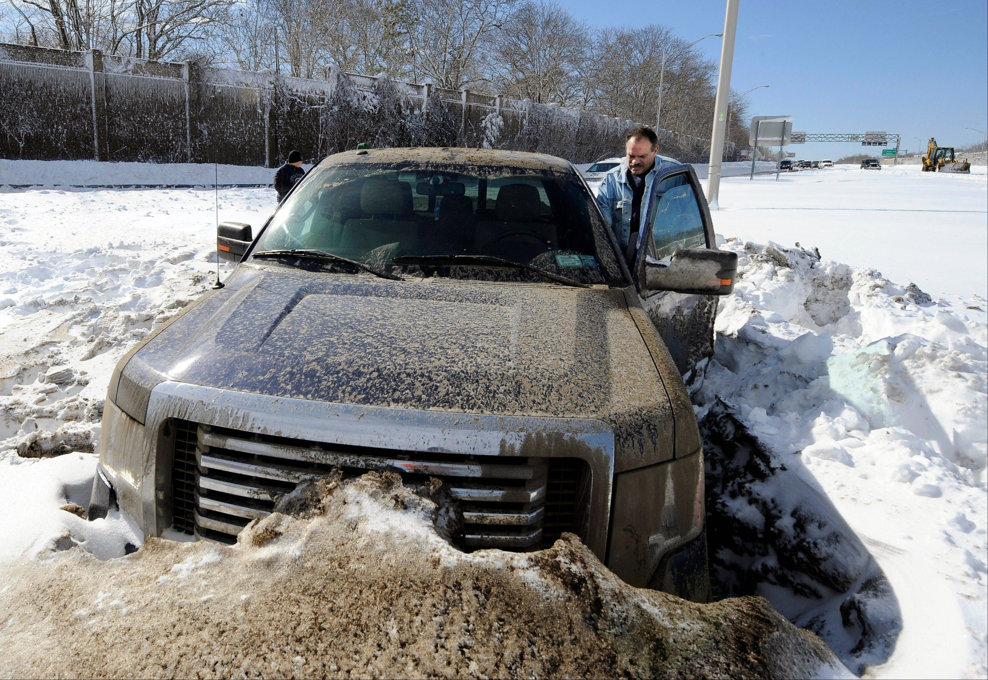 Wayne Gingo, of Medford, N.Y., gets back into his car that got stuck in the snow on the Long Island Expressway eastbound near Exit 60, Saturday, in Ronkonkoma, N.Y. Gingo was driving home from his job as a postal worker at JFK Airport and got stuck in the snow at 1:45 a.m. He spent the night in the car waiting for a tow truck.