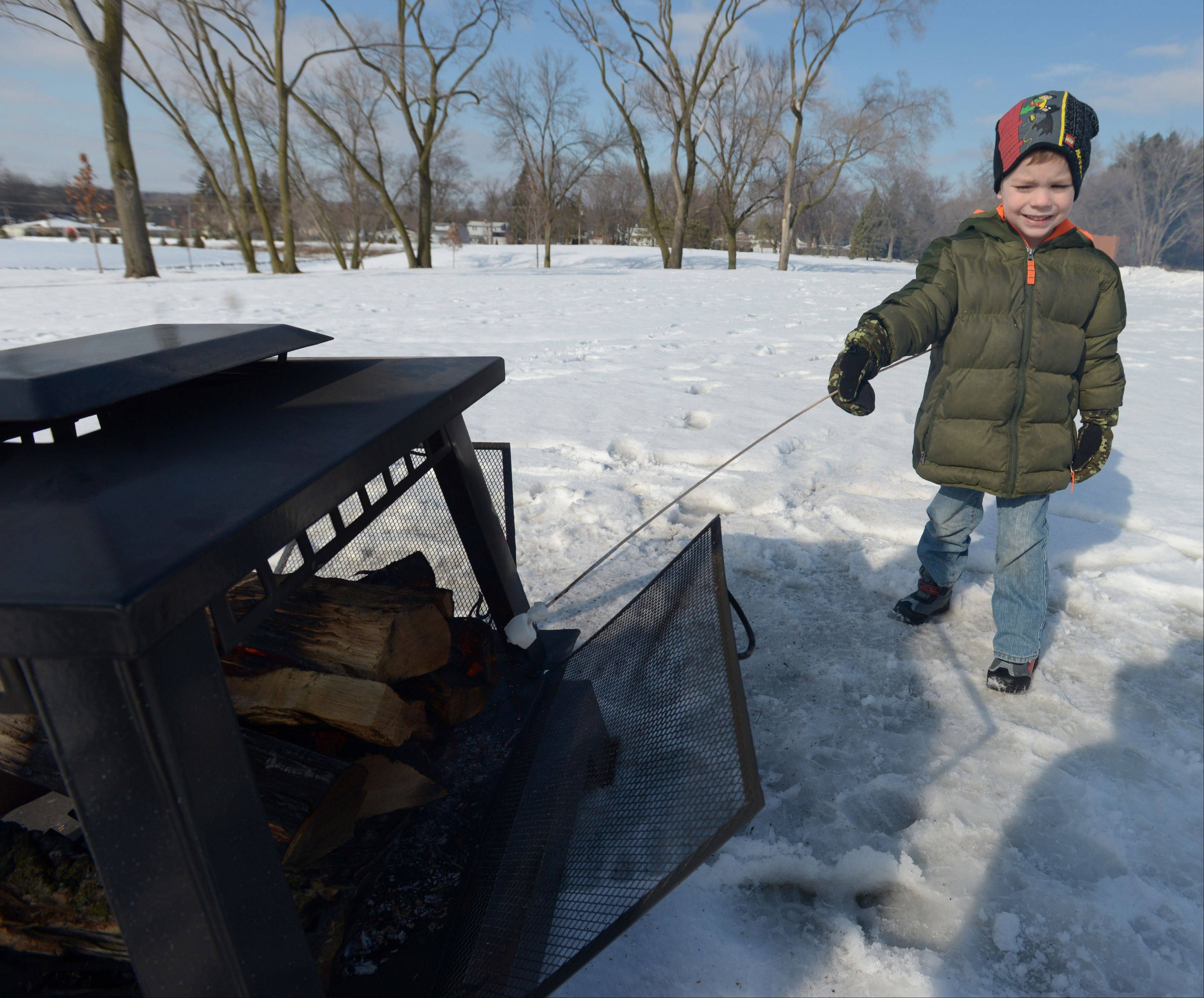 Joshua Push, 4, of Glen Ellyn, roasts a marshmallow Saturday afternoon at the Lombard Park District's annual Winter Carnival. The carnival featured games, ice carving demonstrations and outdoor train rides for kids.