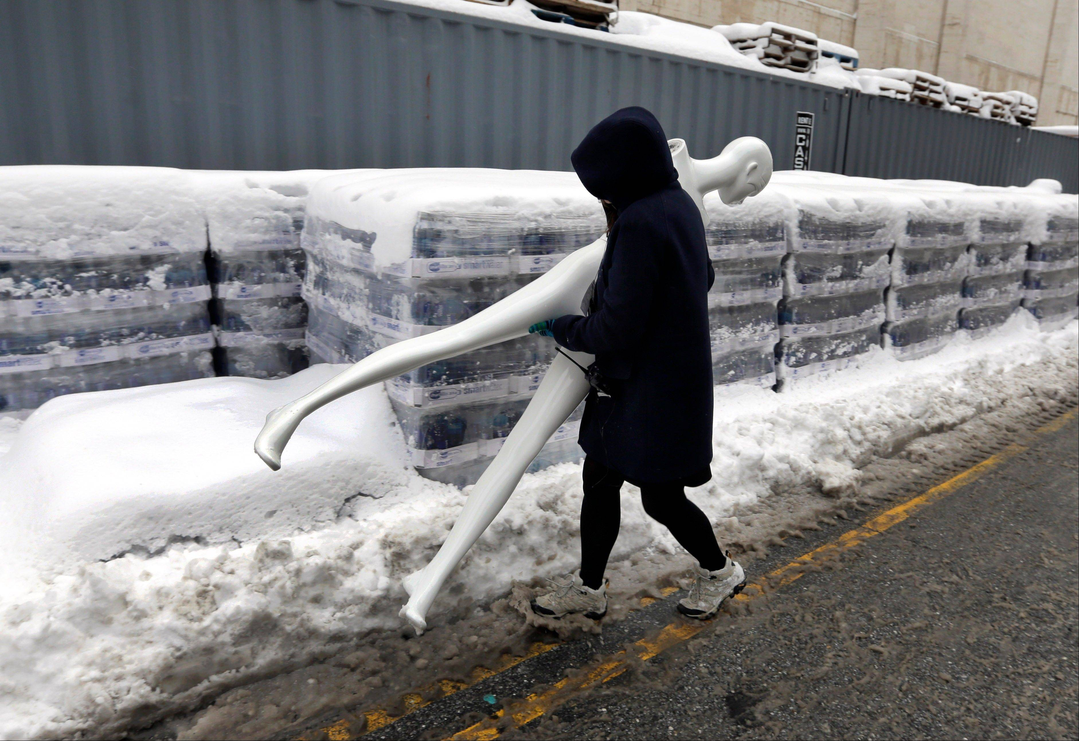 A worker carries a mannequin outside Lincoln Center, home of New York's Fashion Week shows, Saturday. In New York City, the snow total in Central Park was 8.1 inches by 3 a.m.