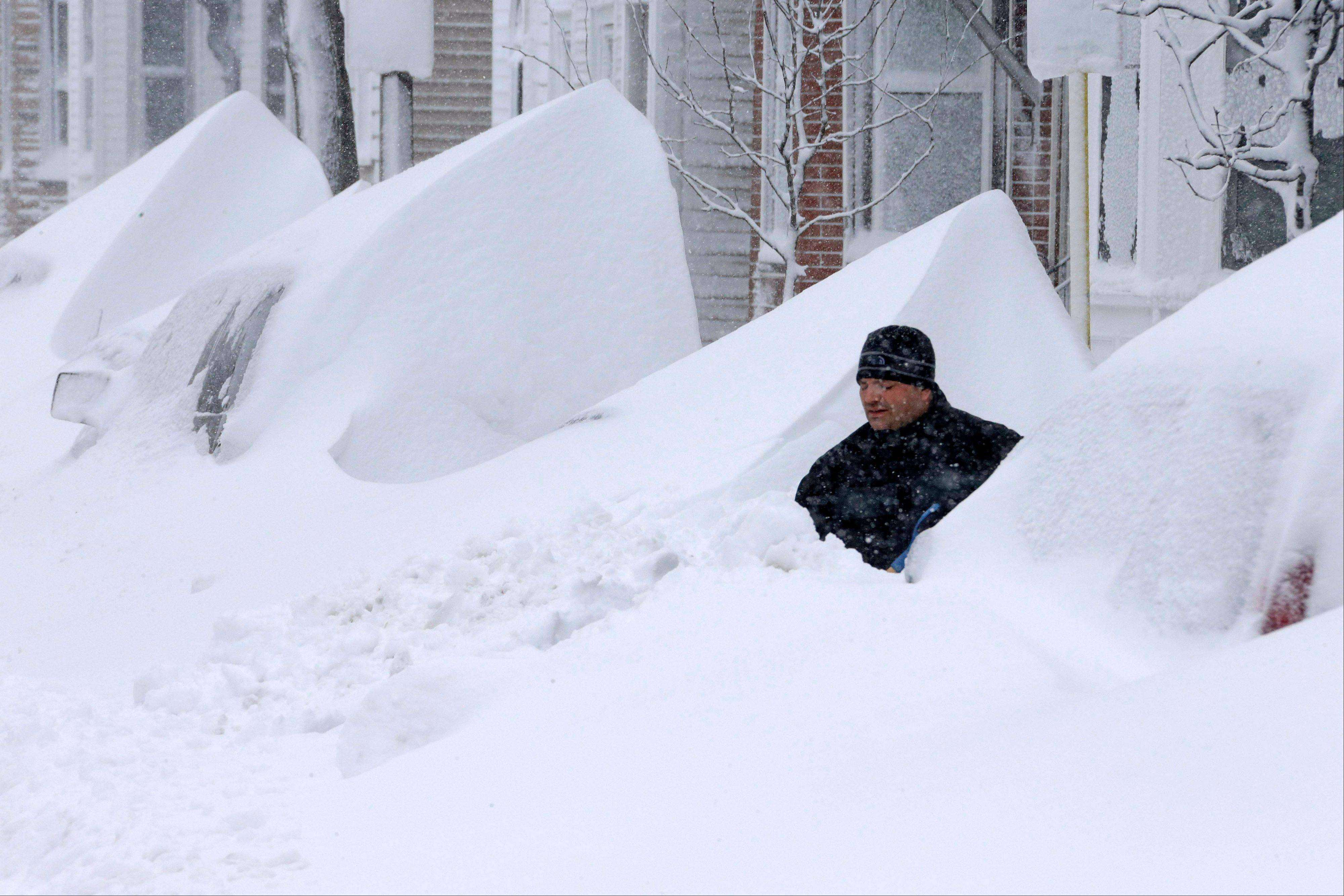 John Silver shovels snow between buried cars in front of his home on Third Street in South Boston, Saturday.