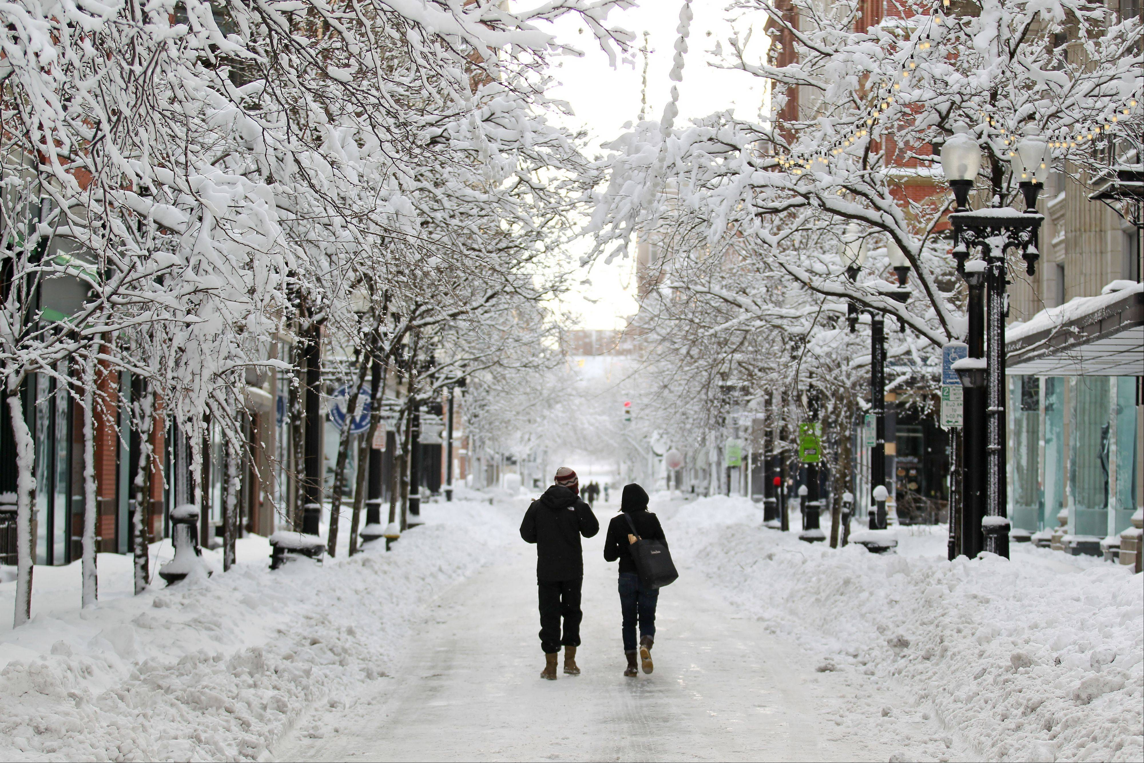 A couple walks down Westminster Street in downtown Providence, R.I., after a winter storm dumped two feet of snow on the area, Saturday.