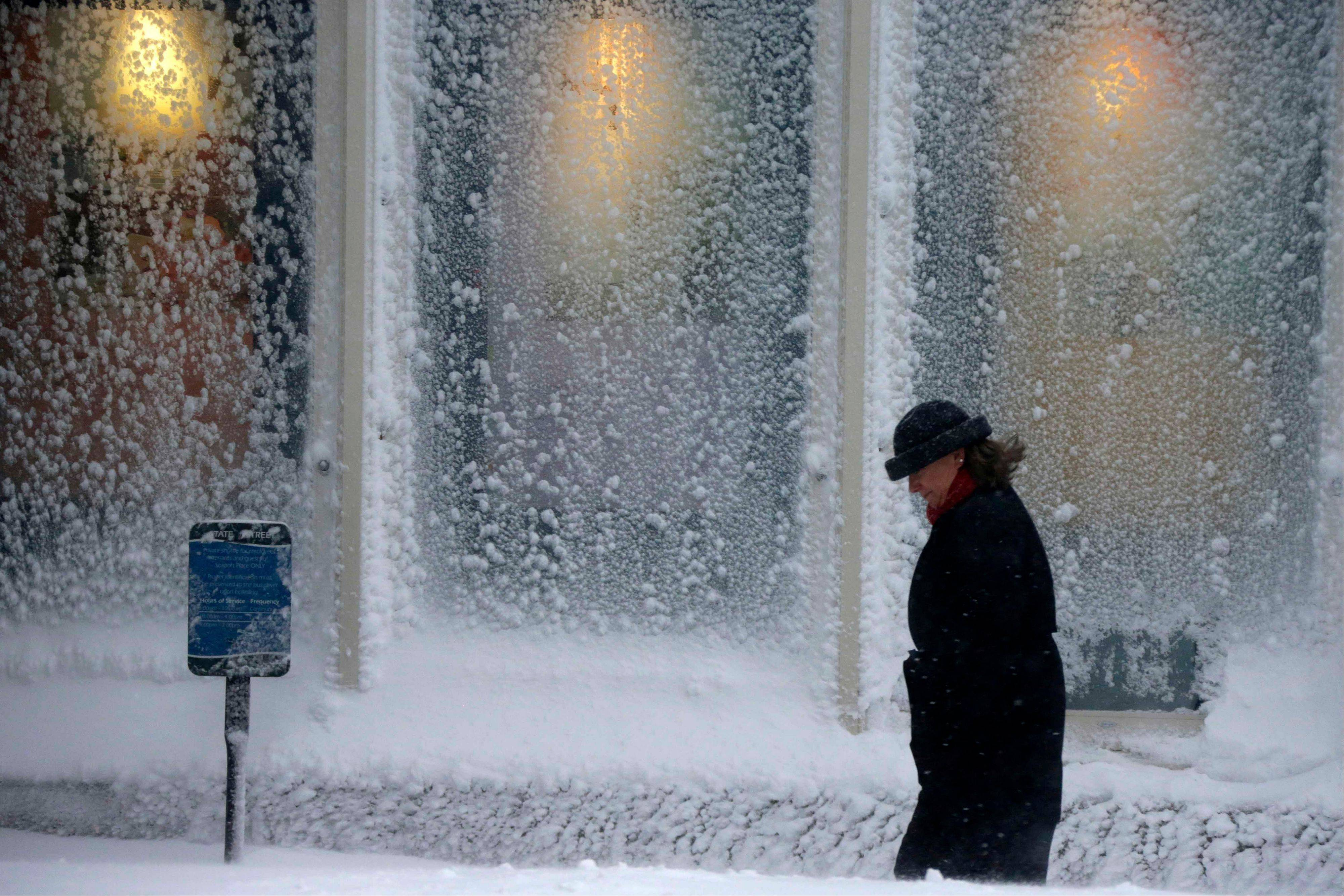 A woman walks past windows covered with snow at the Seaport World Trade Center in Boston early Saturday, Feb. 9, 2013.