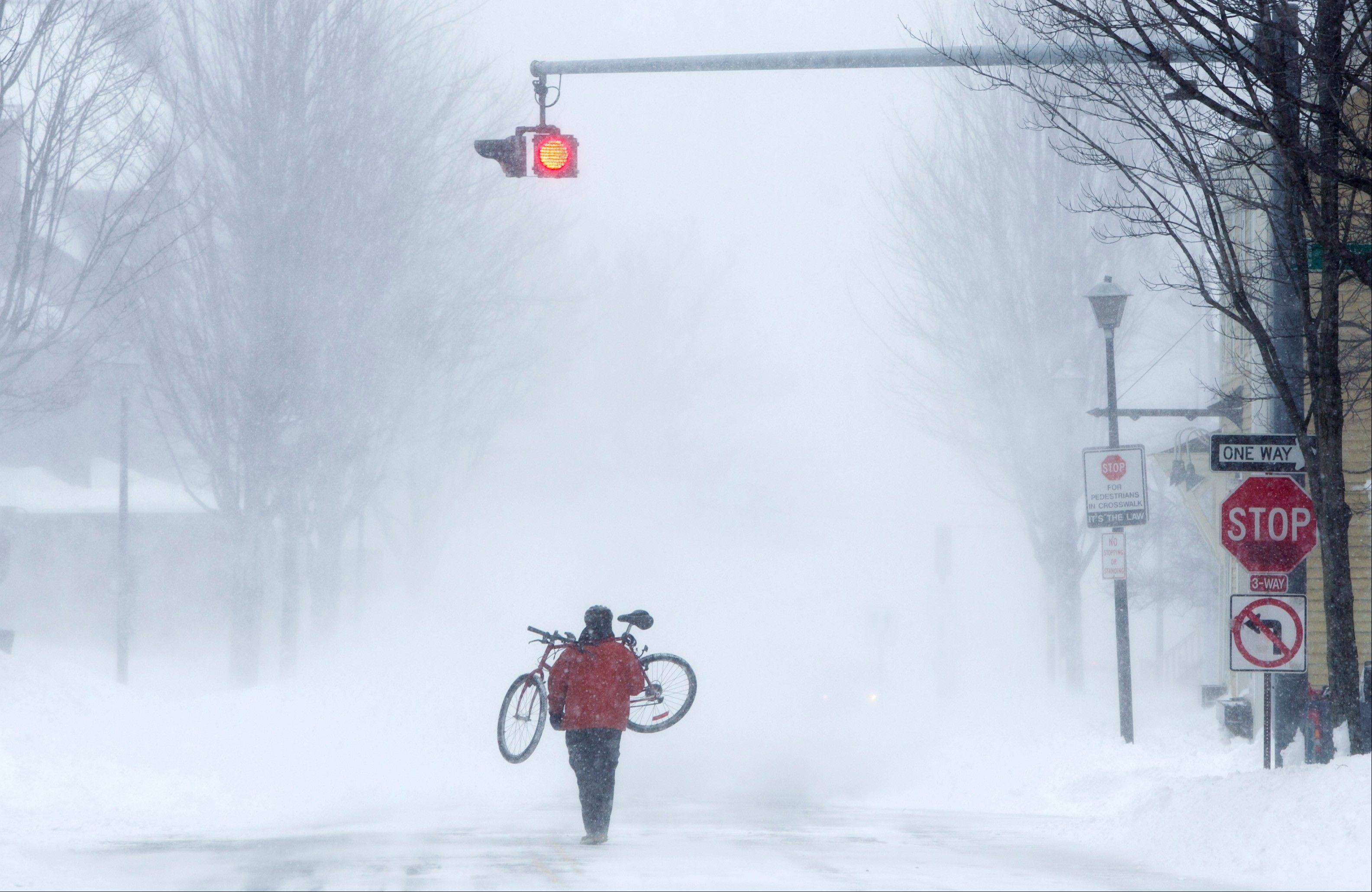 Juan Tavares carries his bike rather than risk riding on a snow-covered street during a blizzard, Saturday, Feb. 9, 2013, in Portland, Maine. The storm dumped more than 30 inches of snow as of Saturday afternoon, breaking the record for the biggest storm on record.