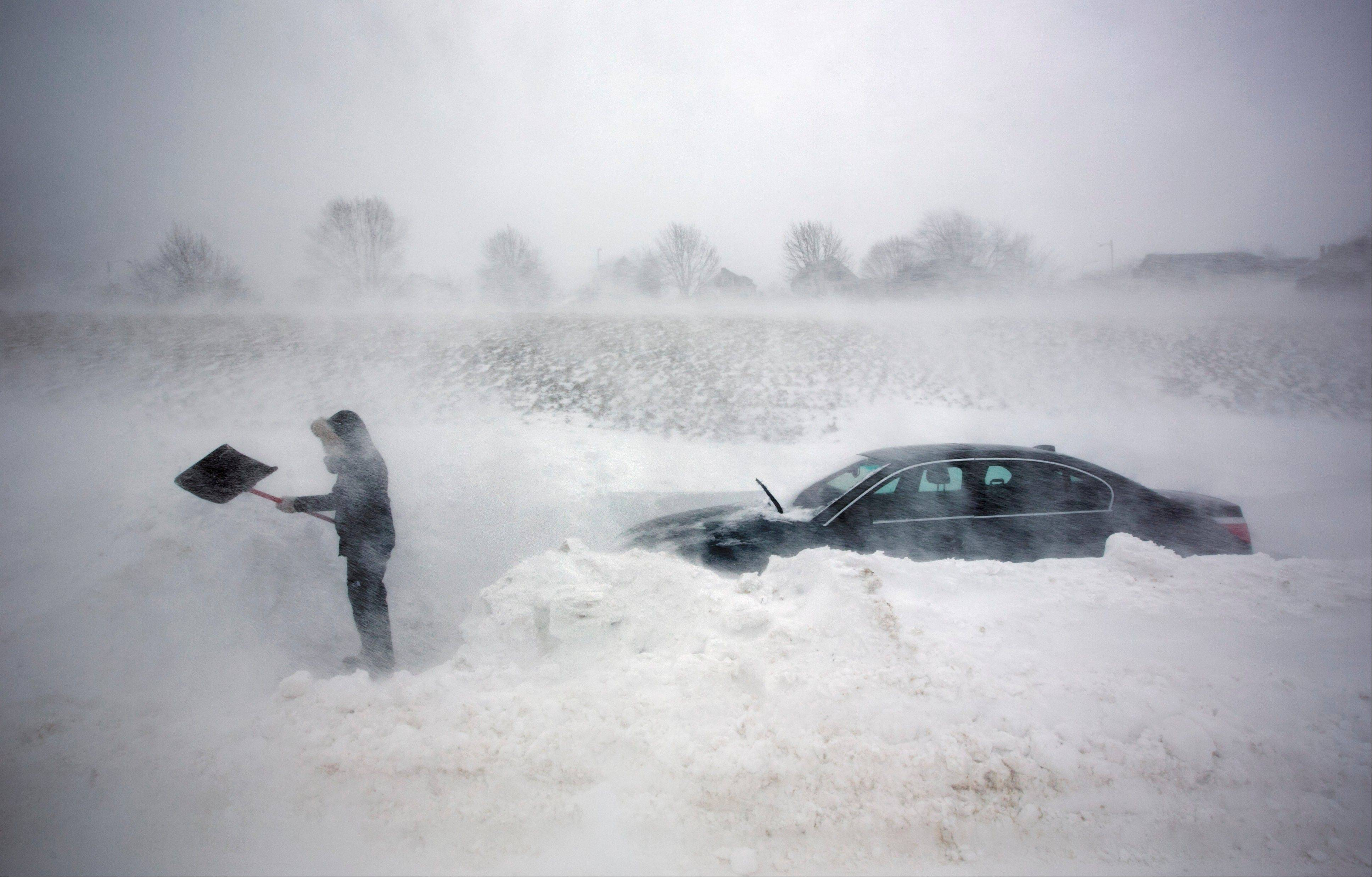 A woman digs out her car after it was blocked in by drifting snow during a blizzard, Saturday, Feb. 9, 2013, in Portland, Maine. The storm dumped more than 30 inches of snow as of Saturday afternoon, breaking the record for the biggest storm on record.