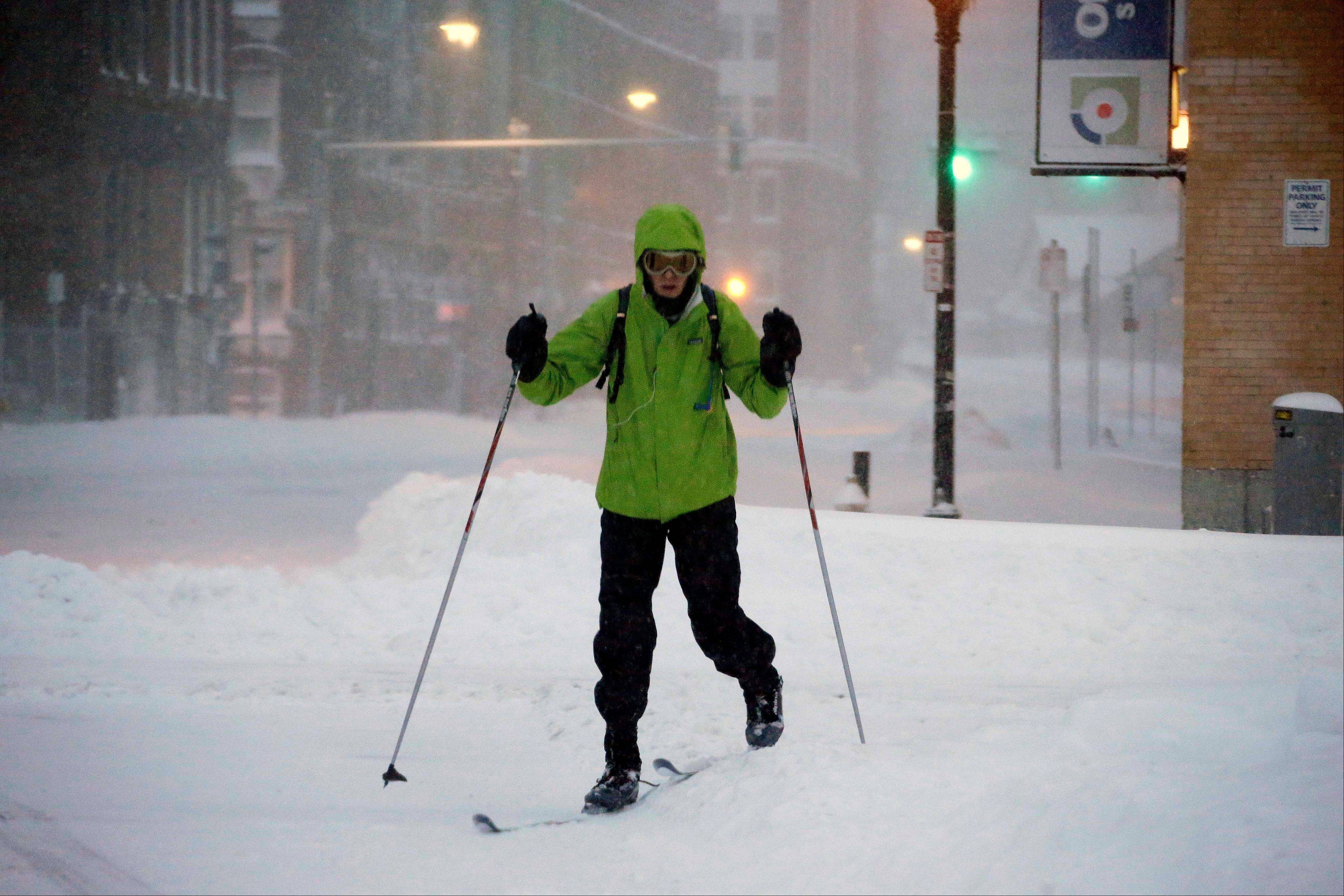 A pedestrian uses skis to travel through the deserted snow-covered streets of Boston early Saturday, Feb. 9, 2013.