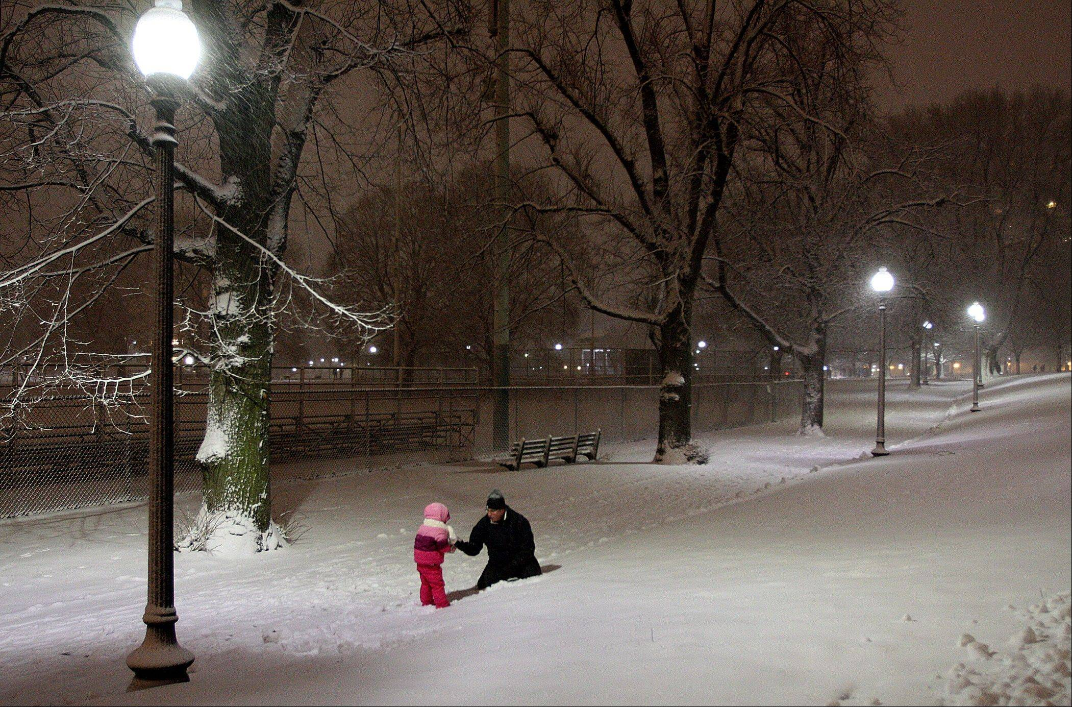 A father plays with his son on Boston Common in Boston, during a snowstorm Friday evening, Feb. 8, 2013. Snow began to fall as a massive blizzard headed for the American Northeas, sending residents scurrying to stock up on food and supplies ahead of a storm poised to dump up to 3 feet of snow from New York City to Boston and beyond.
