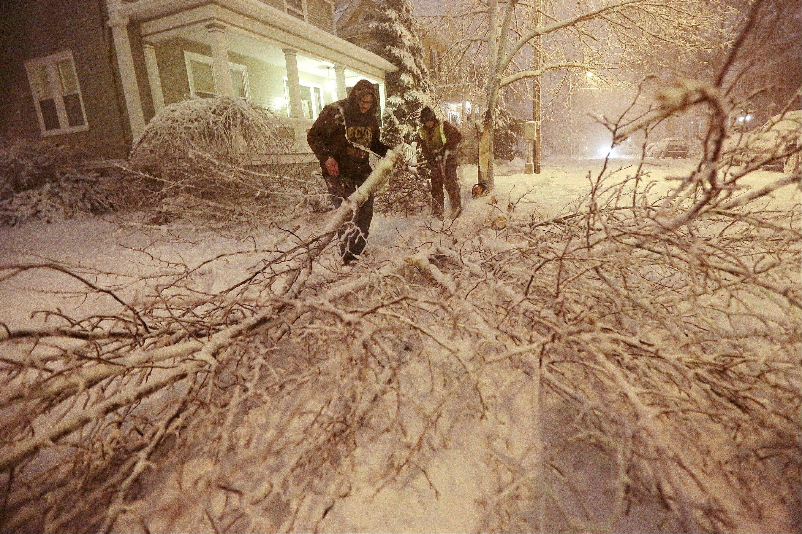 Mike Williams, left, and Louie Rodriguez of the New Bedford Forestry Department clear out a fallen tree from an intersection in New Bedford, Mass., on Friday, Feb. 8, 2013, after heavy snow and winds from a storm.