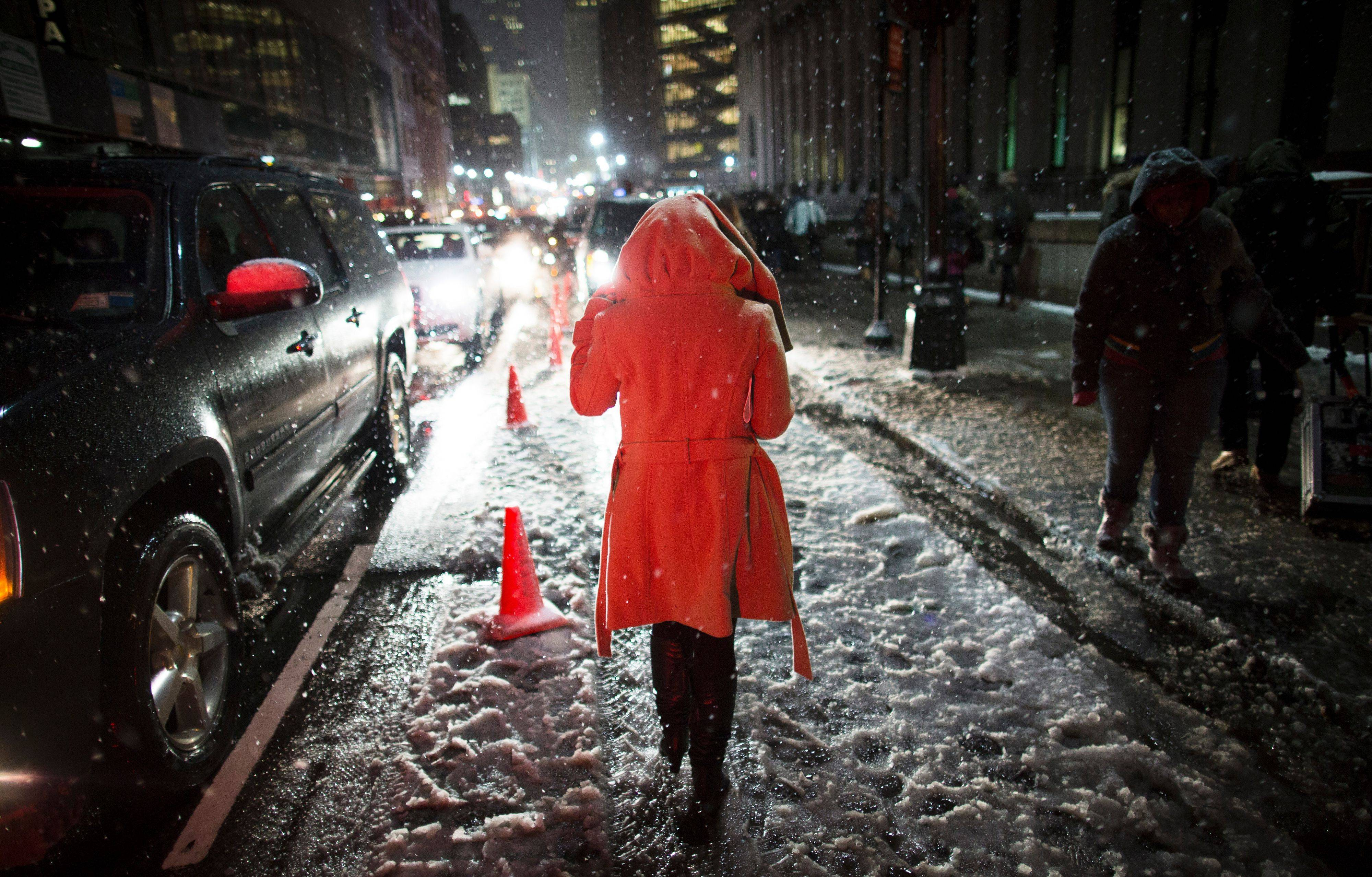 Snow falls on a pedestrian as she leaves the Rag & Bone Fall 2013 fashion collection show during Fashion Week, Friday, Feb. 8, 2013, in New York. Snow began falling across the Northeast on Friday, ushering in what was predicted to be a huge, possibly historic blizzard and sending residents scurrying to stock up on food and gas up their cars.