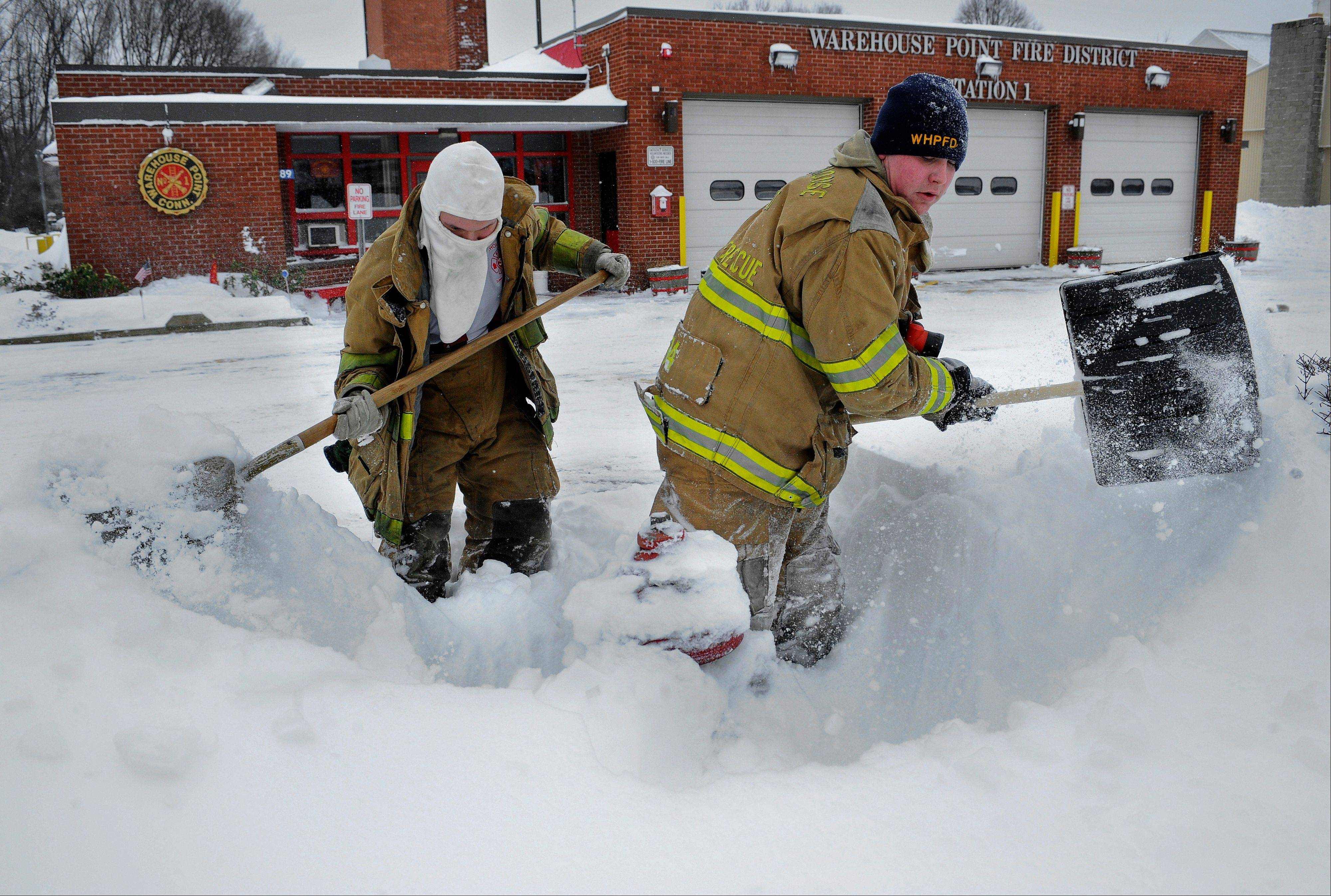 Junior firefighter Adam Krach, left, and firefighter Steve Ellis of the Warehouse Point Fire Department dig snow from a hydrant outside their station in East Windsor, Conn. on Saturday, Feb. 9, 2013. A behemoth storm packing hurricane-force wind gusts and blizzard conditions swept through the Northeast overnight.