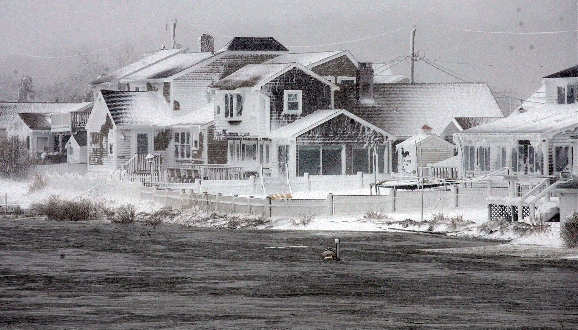 Wet snow coats houses along the South River at high tide in the Humarock coastal neighborhood of Scituate Mass. on Saturday, Feb. 9, 2013. A behemoth storm packing hurricane-force wind gusts and blizzard conditions swept through the Northeast overnight.