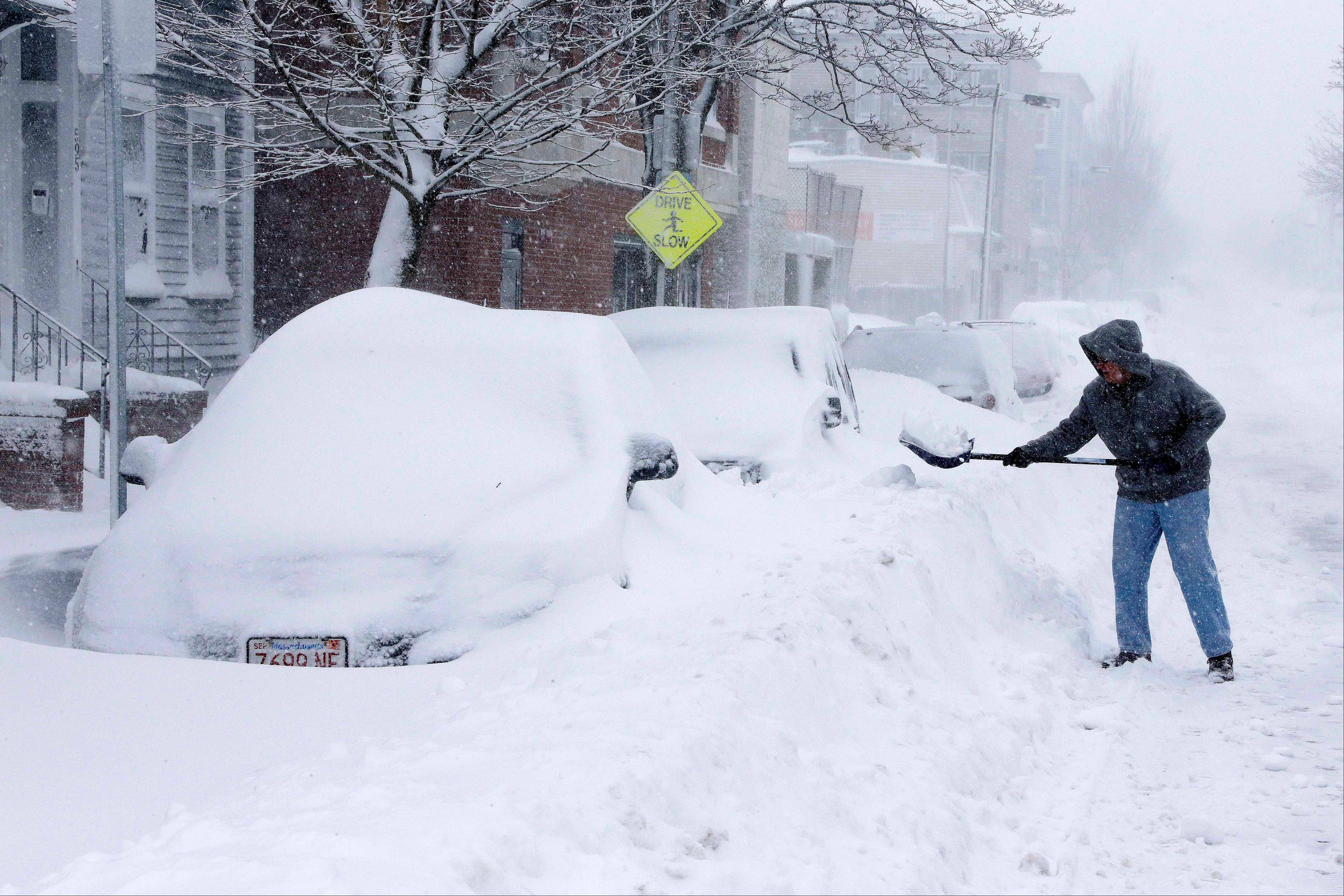 A man shovels out a car on Third street in the South Boston neighborhood of Boston, Saturday, Feb. 9, 2013. A behemoth storm packing hurricane-force wind gusts and blizzard conditions swept through the Northeast on Saturday, dumping more than 2 feet of snow on New England and knocking out power to 650,000 homes and businesses.