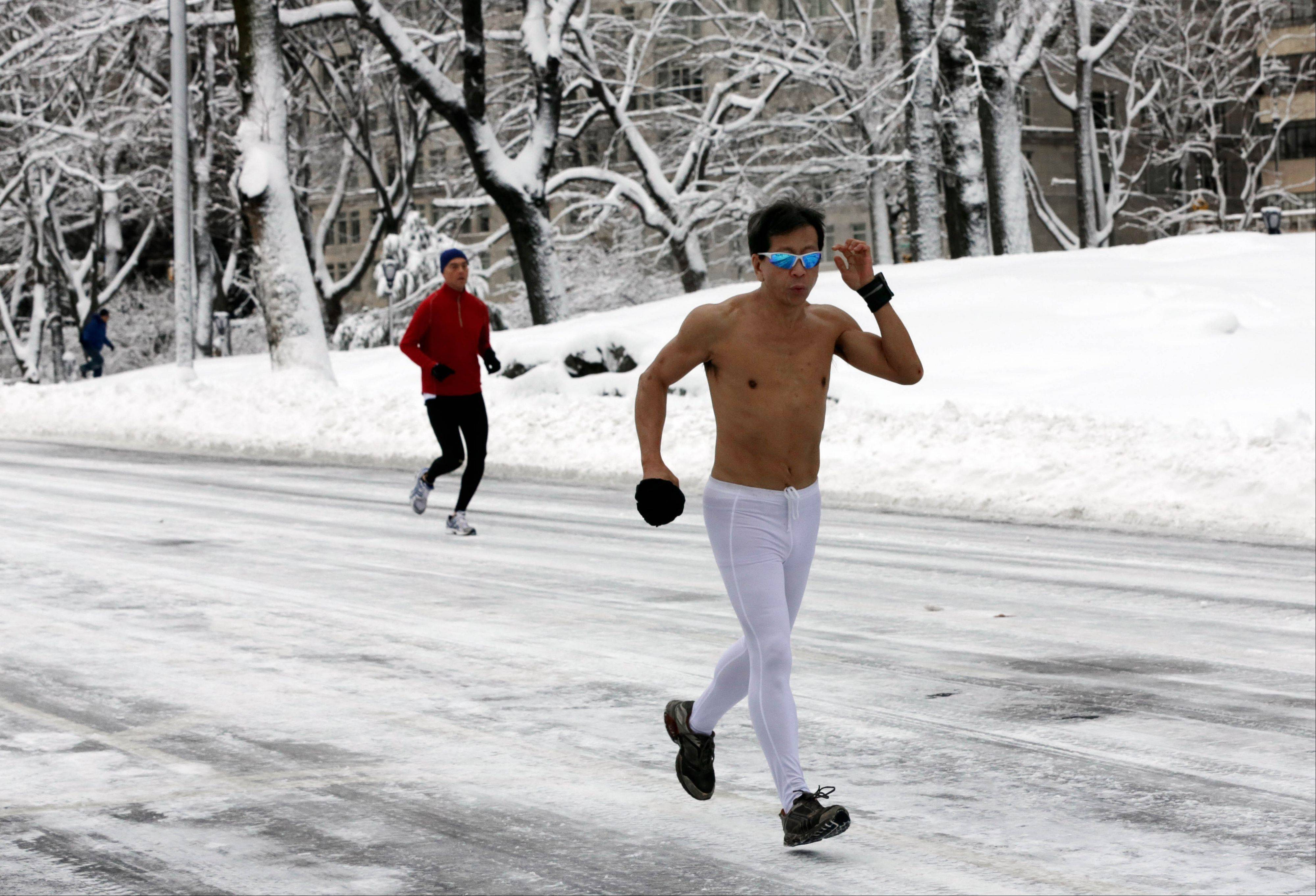 A shirtless jogger runs through New York's Central Park Saturday, Feb. 9, 2013. In New York City, the snow total in Central Park was 11.4 inches by 8 a.m.