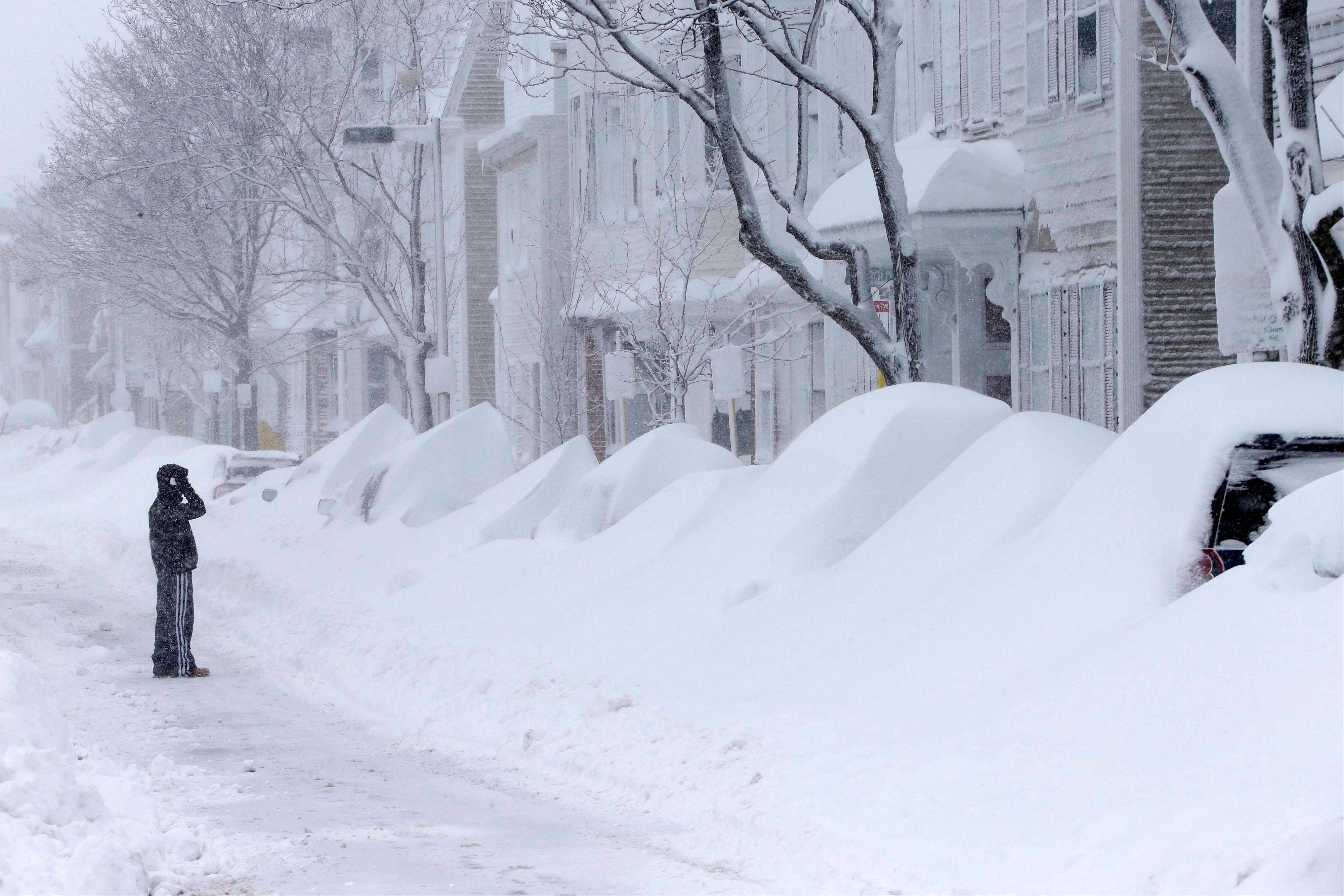 A man talks on the phone as he looks at a row of cars buried in snow on Third Street in the South Boston neighborhood of Boston Saturday, Feb. 9, 2013.