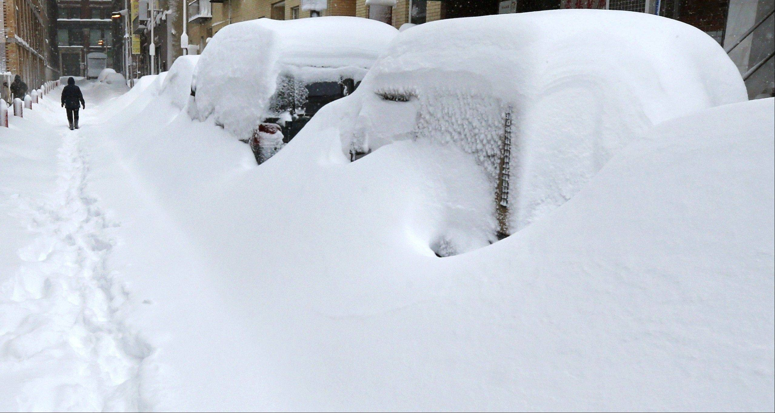 A man walks past snow covered cars in the Chinatown neighborhood of Boston, Saturday, Feb. 9, 2013. The Boston area received about two feet of snow from a winter storm.