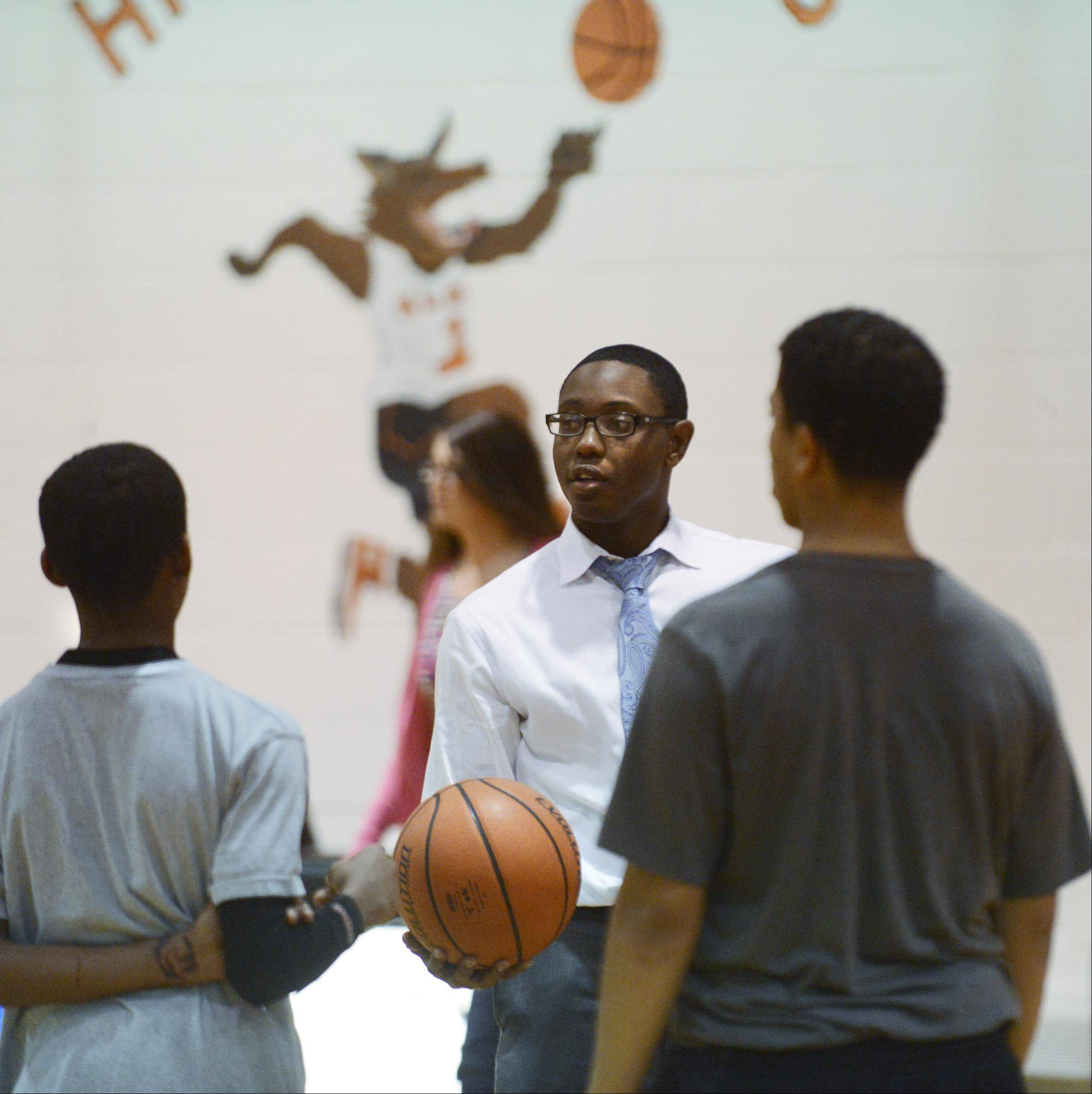 Justin Anthony and Josie Wallace, background, are founders of Epic Youth, a new Christian-based program in Elgin that focuses on using basketball to develop leadership skills and encourage kids to attend college.