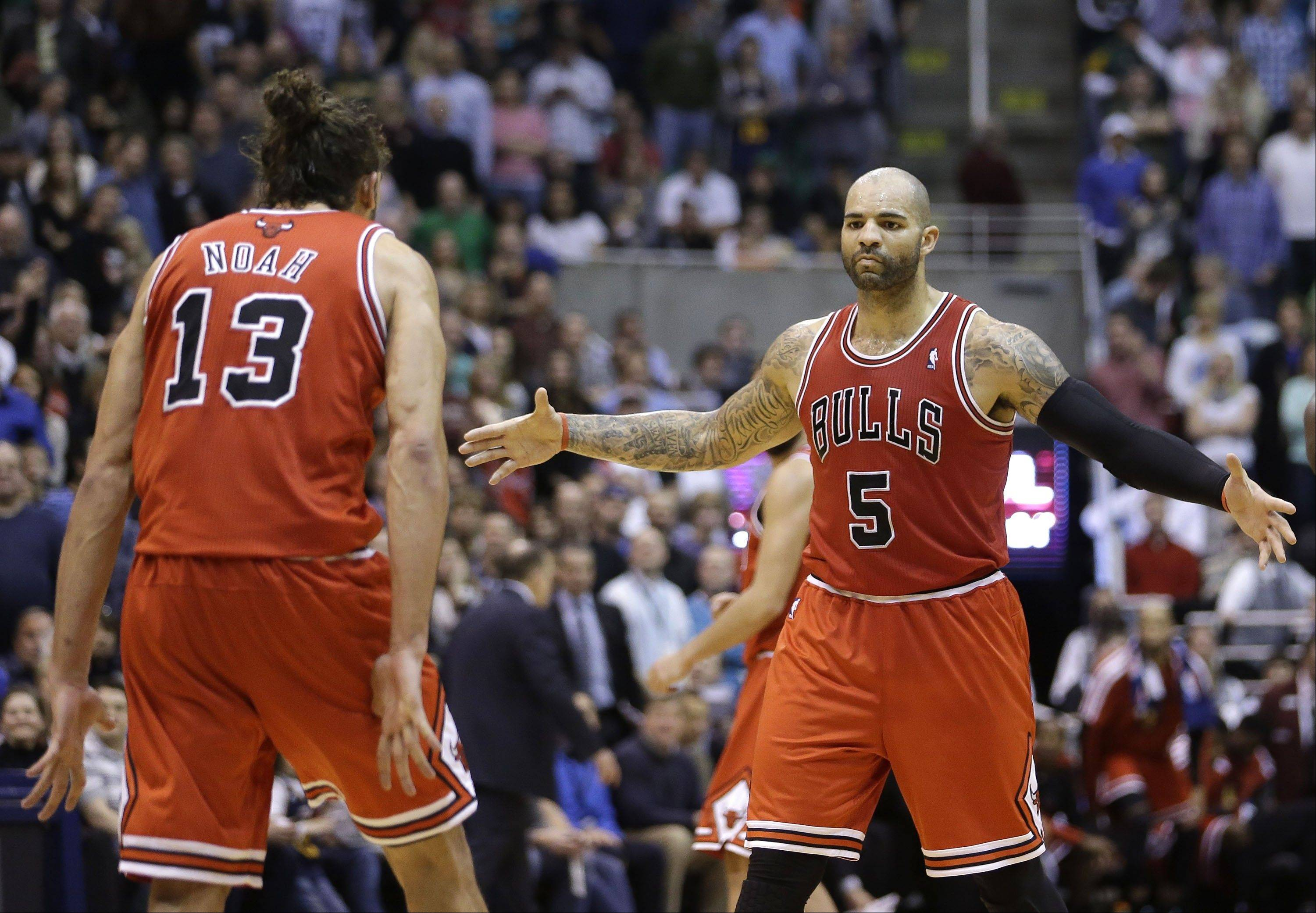 Joakim Noah (13) and Carlos Boozer celebrate in the fourth quarter of the Bulls' victory Friday night in Utah. Boozer scored 11 of his 19 points in the last five minutes.