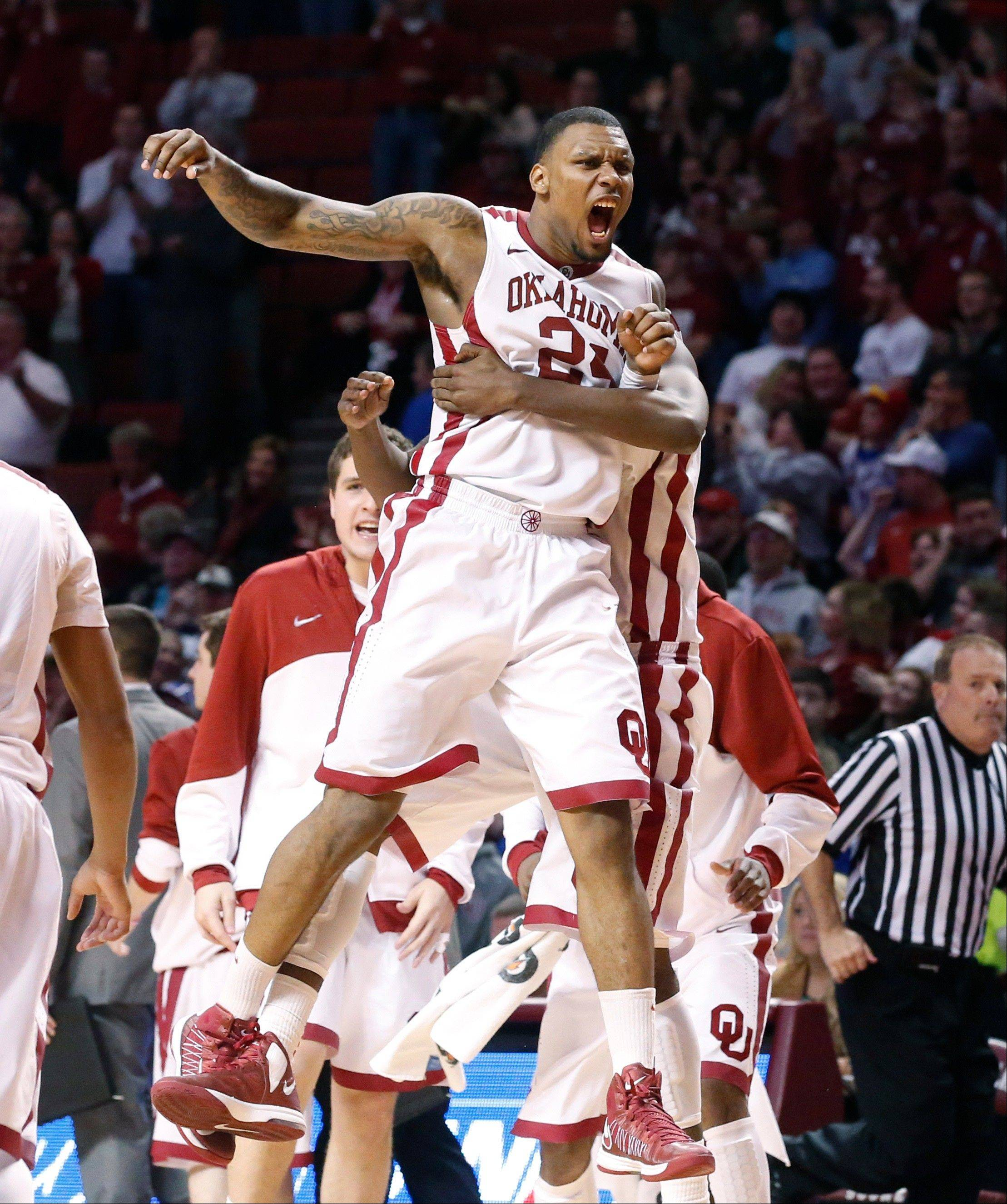 Oklahoma forward Romero Osby (24) jumps into the arms of teammate Andrew Fitzgerald, rear, at the end of the game as Oklahoma defeated Kansas 72-66 in an NCAA college basketball game in Norman, Okla., Saturday, Feb. 9, 2013.