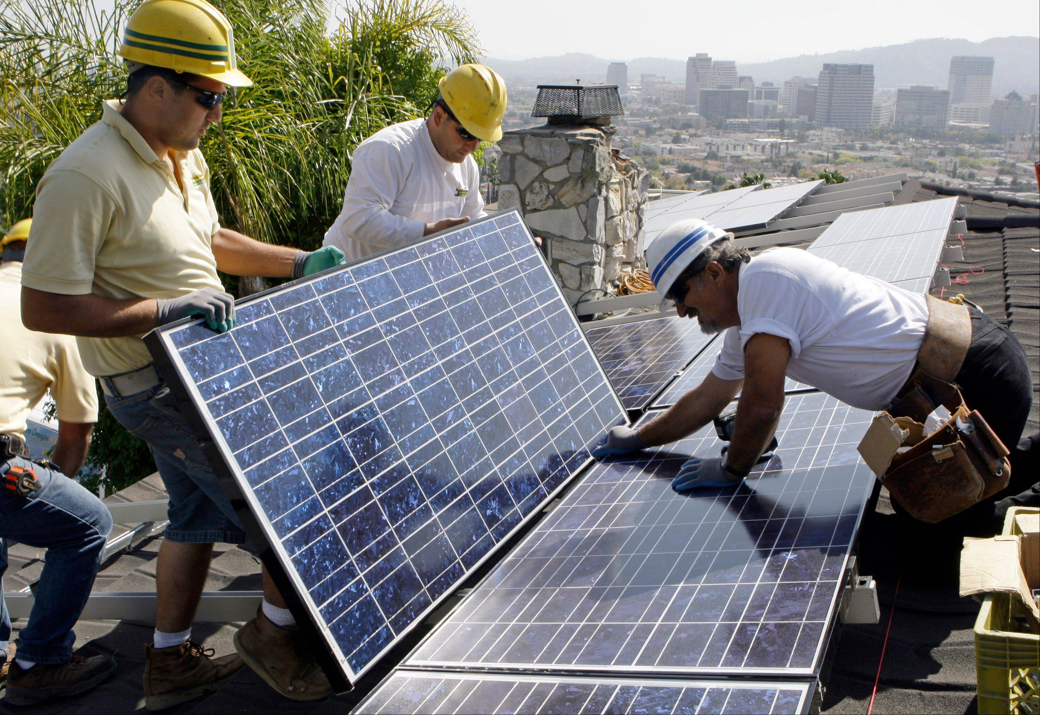 In this file photo taken in 2010, employees of California Green Design assemble solar electrical panels on the roof of a home in Glendale, Calif.