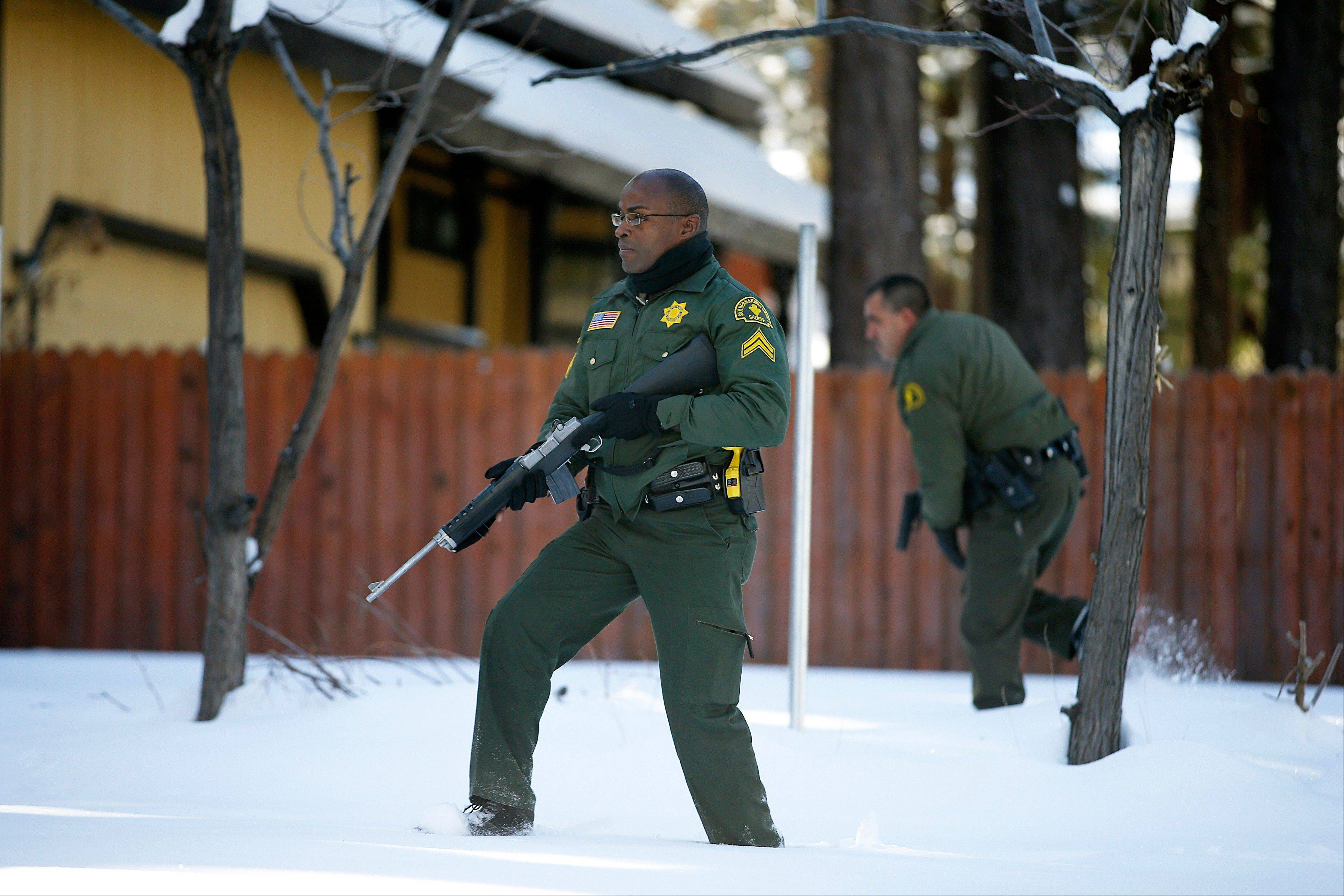 San Bernardino County sheriff�s officers Ken Owens, center, and Bernabe Ortiz search for former Los Angeles police officer Christopher Dorner on Sunday in Big Bear Lake, Calif.