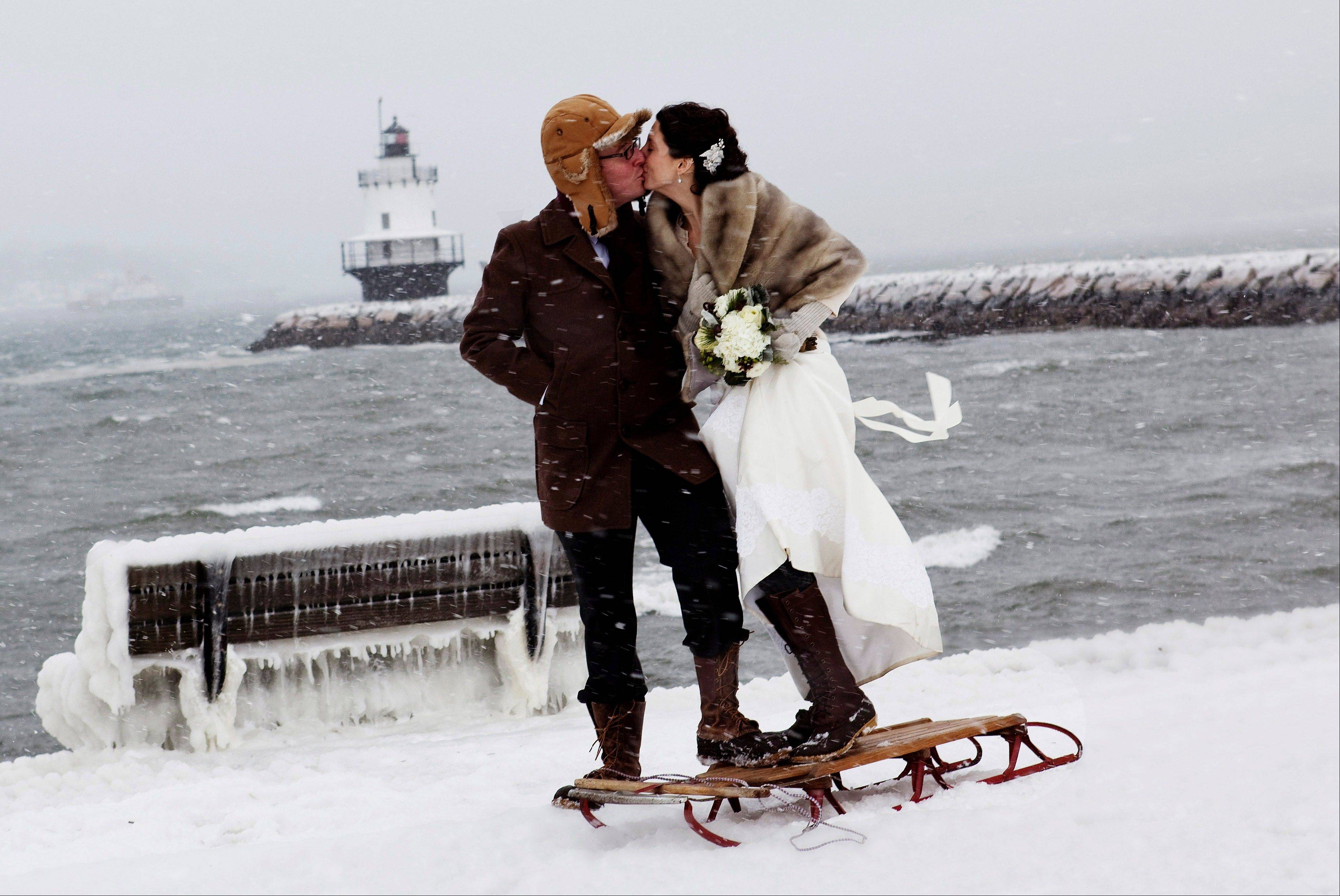 Greg Beal and Karen Willis Beal pose for photos outdoors after their wedding that went on despite a snowstorm in South Portland, Maine. Karen Willis Beal said her vision of a dream wedding included a snowstorm just like the one hit before her parents married in December 1970.