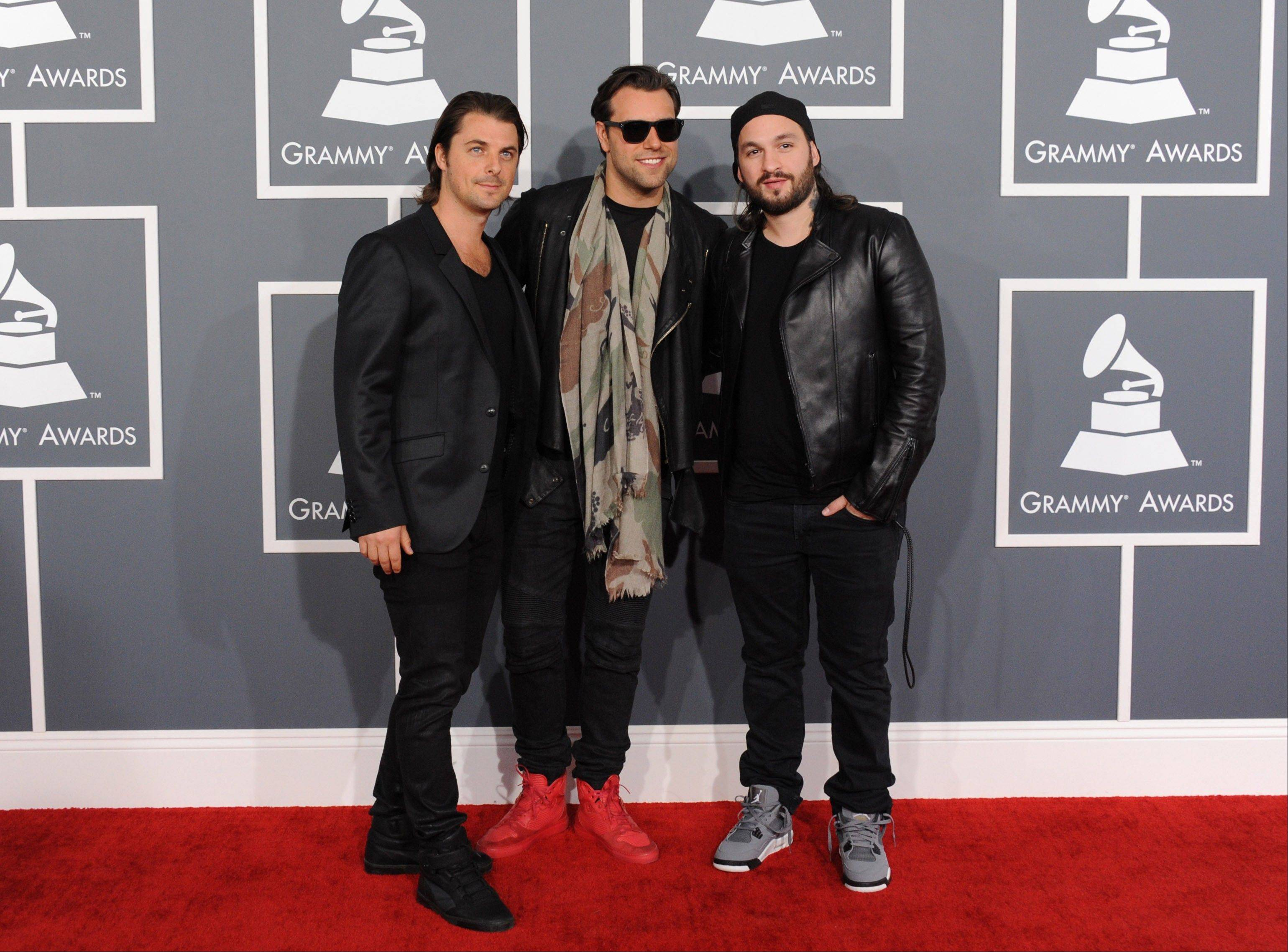 Swedish House Mafia, from left, Axwell, Steve, Sebastian Ingrosso, and Steve Angello arrive at the 55th annual Grammy Awards on Sunday, Feb. 10, 2013, in Los Angeles.