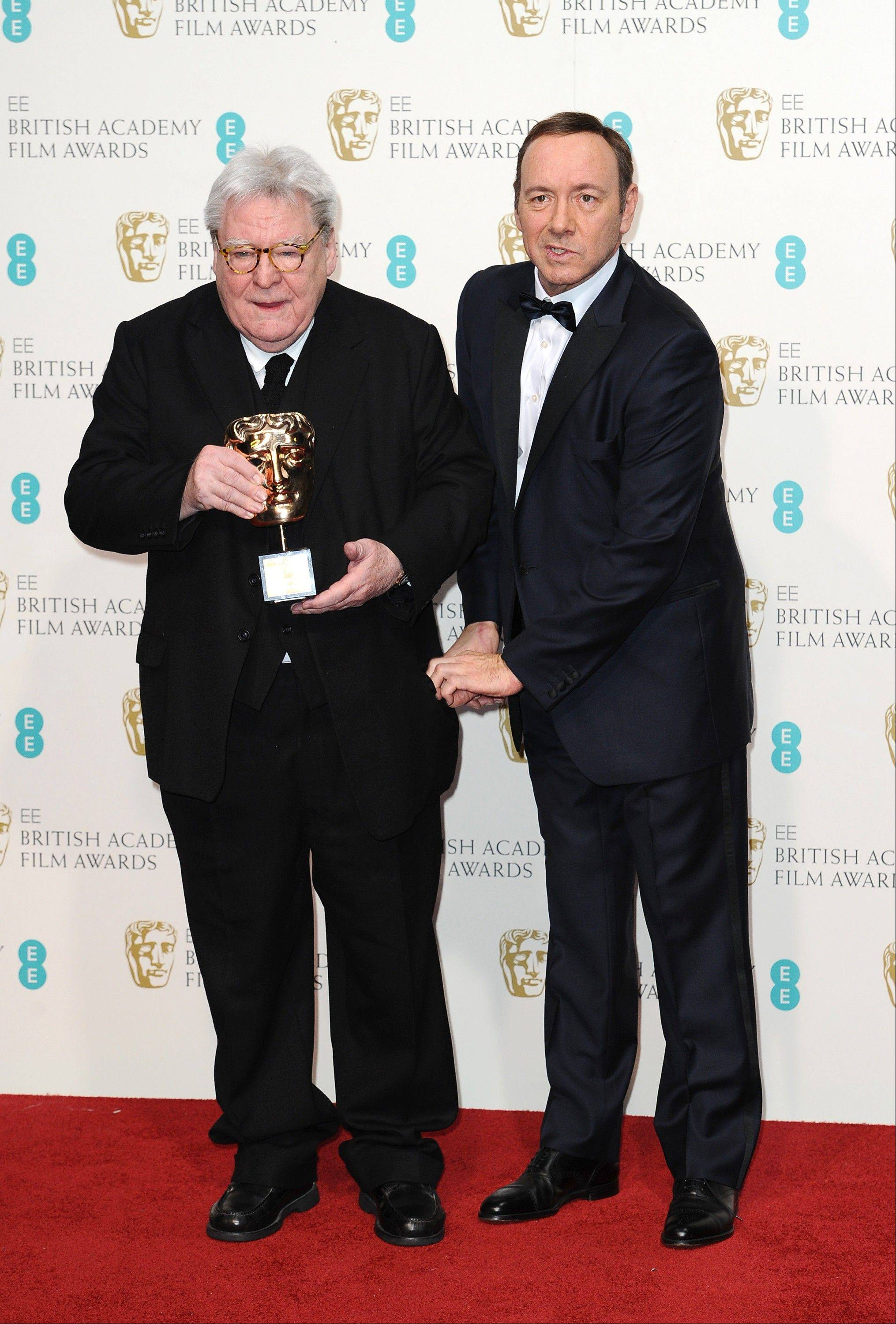 British director Alan Parker, left, with the Fellowship award, and American producer-actor Kevin Spacey pose backstage at the BAFTA Film Awards at the Royal Opera House on Sunday, Feb. 10, 2013, in London.
