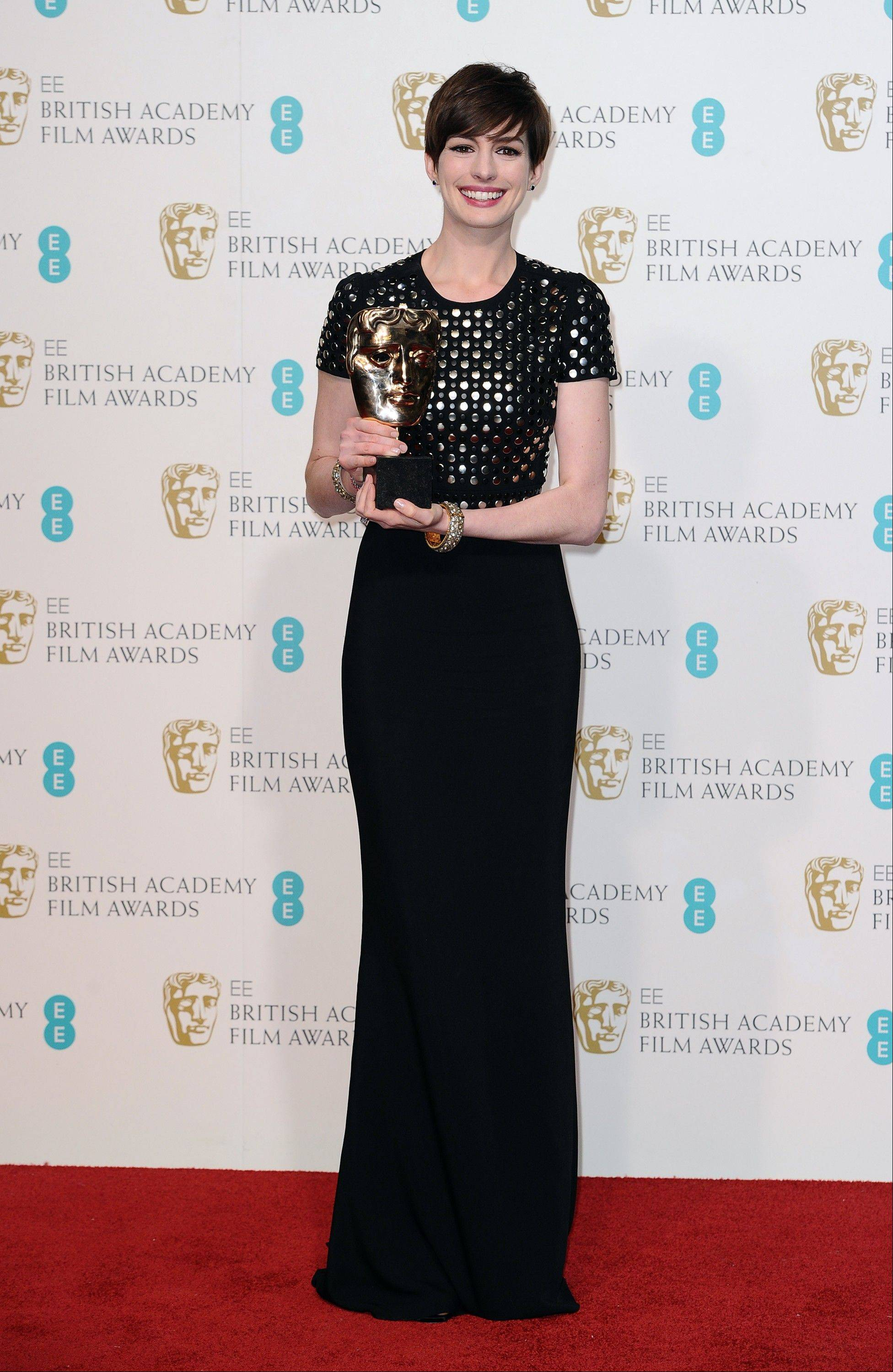 "Actress Anne Hathaway poses backstage with the award for Supporting Actress for her role in ""Les Miserables,"" at the BAFTA Film Awards at the Royal Opera House on Sunday, Feb. 10, 2013, in London."
