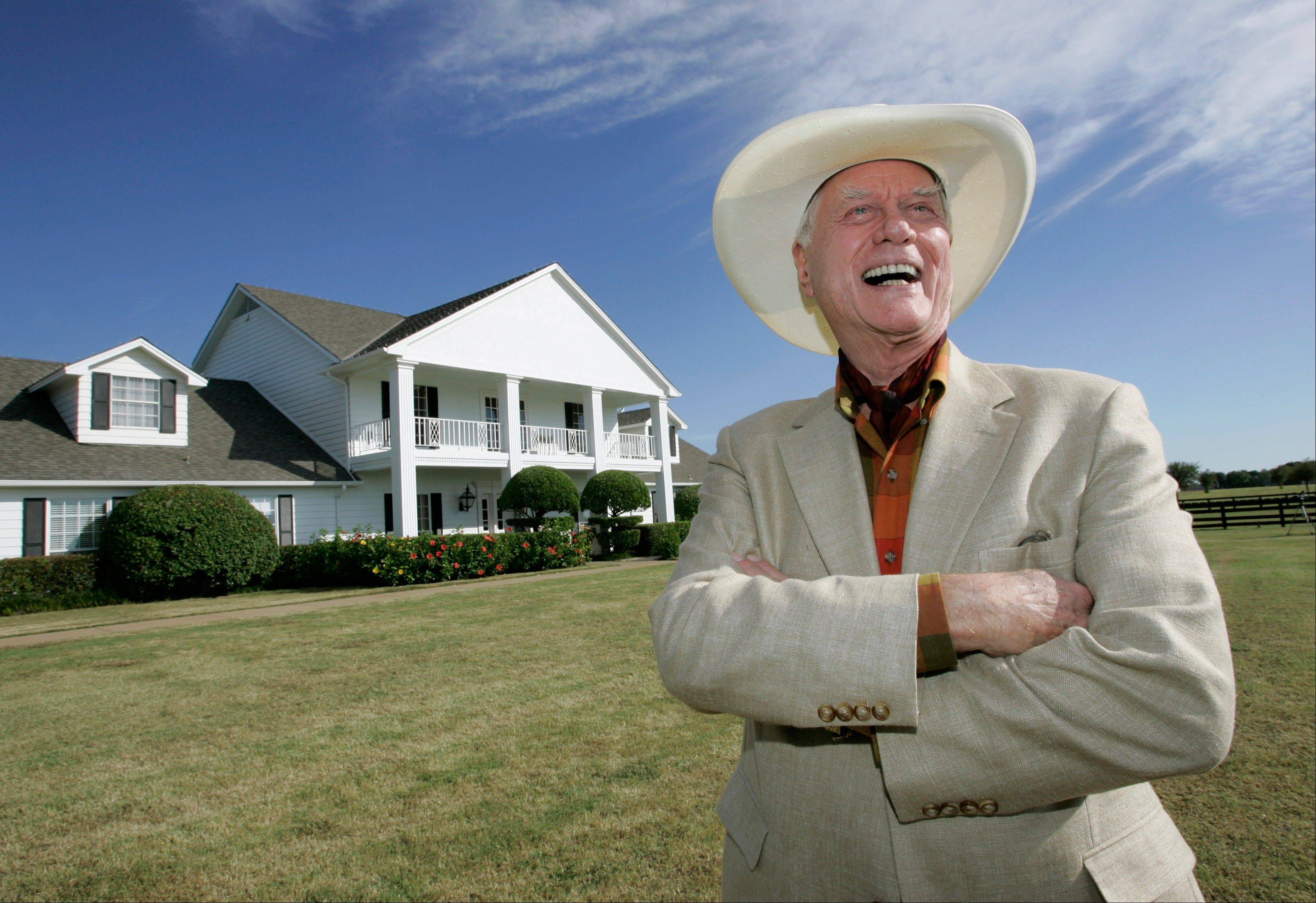 "The late Actor Larry Hagman poses in front of the Southfork Ranch mansion made famous in the television show ""Dallas."" The recent death of the show's star, who legendarily played conniving Texas oilman J.R. Ewing, has spurred more fans to visit."