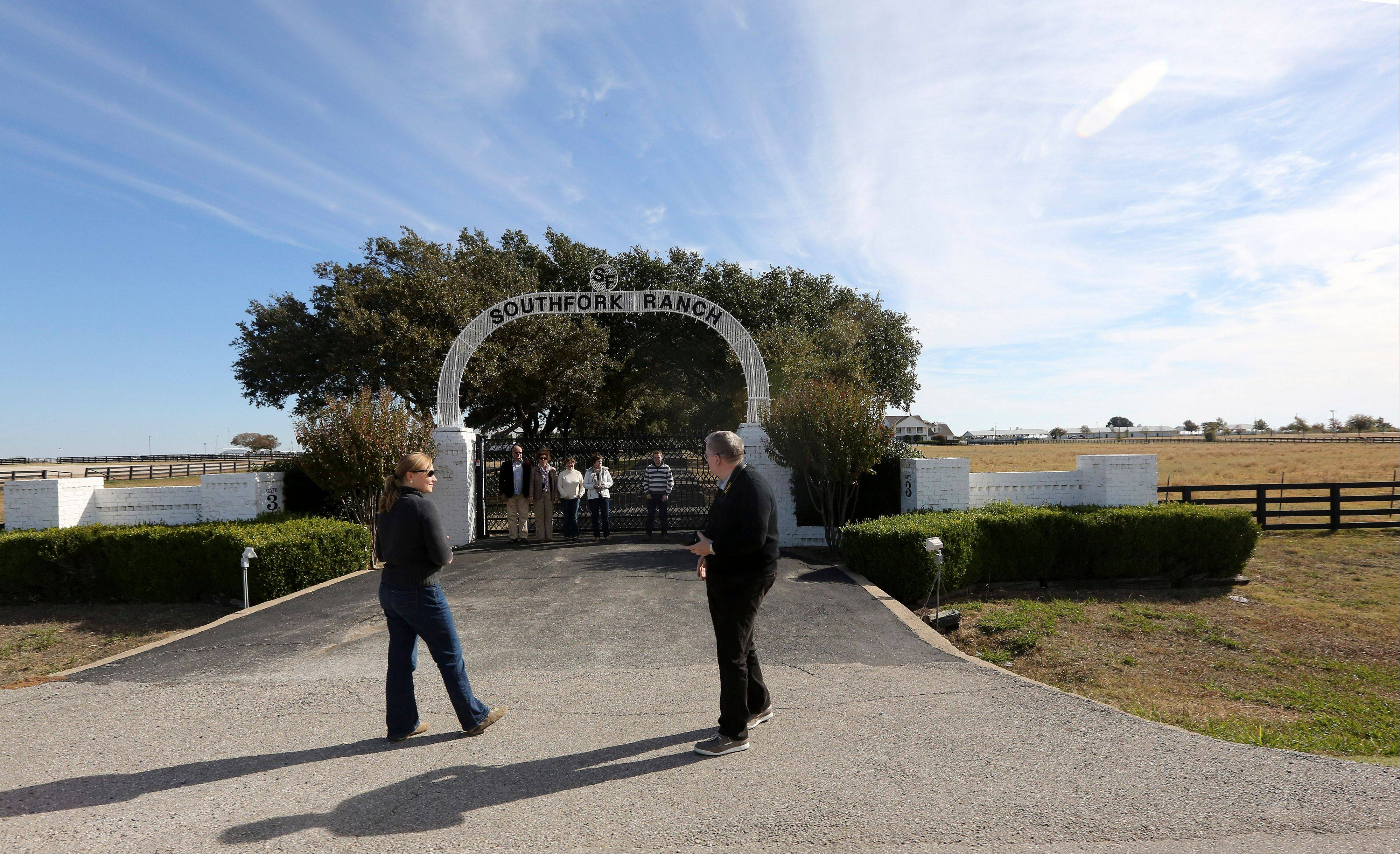 Tourists line up for a photo at the front gate of Southfork Ranch in Parker, Texas.