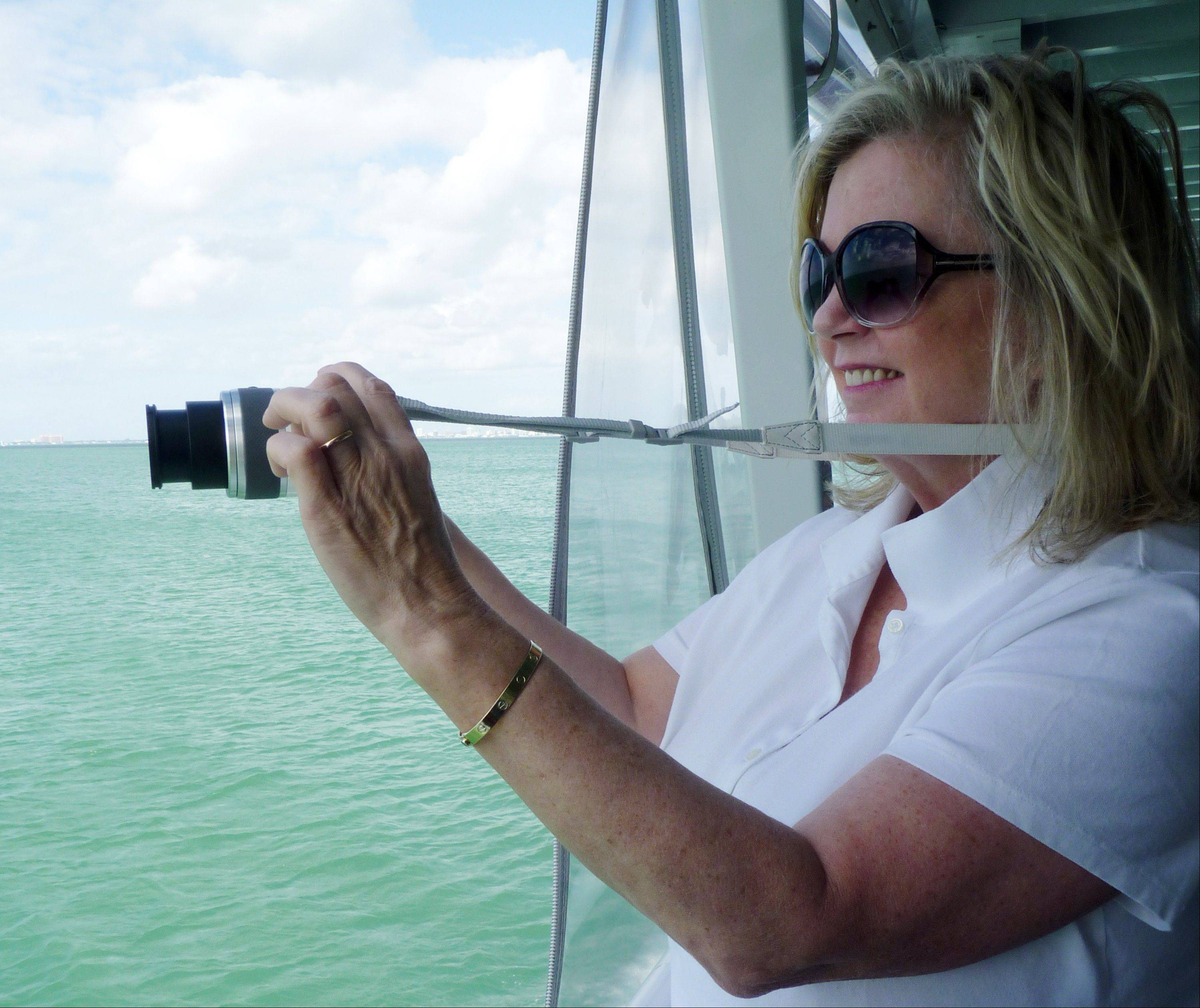 Karen Clark of Saratoga Springs, N.Y., takes a photo of one of the seven Stiltsville homes near Miami.