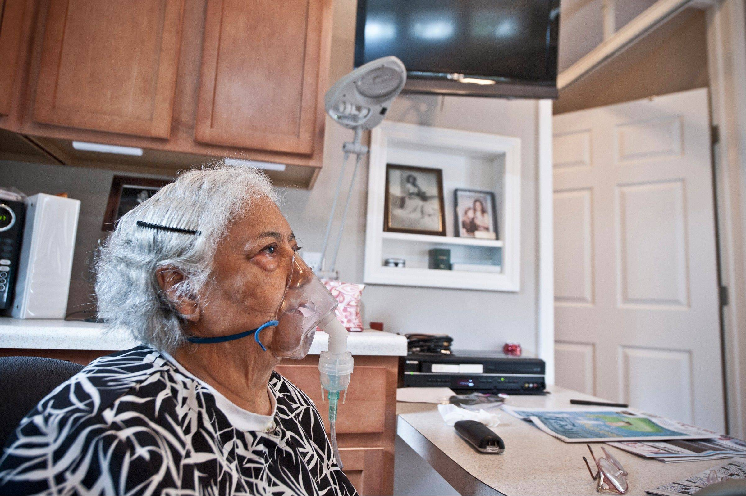 Viola Baez inhales a vapor treatment in the MedCottage installed in her daughter's backyard. The small, high-tech cottages function like portable hospital rooms.